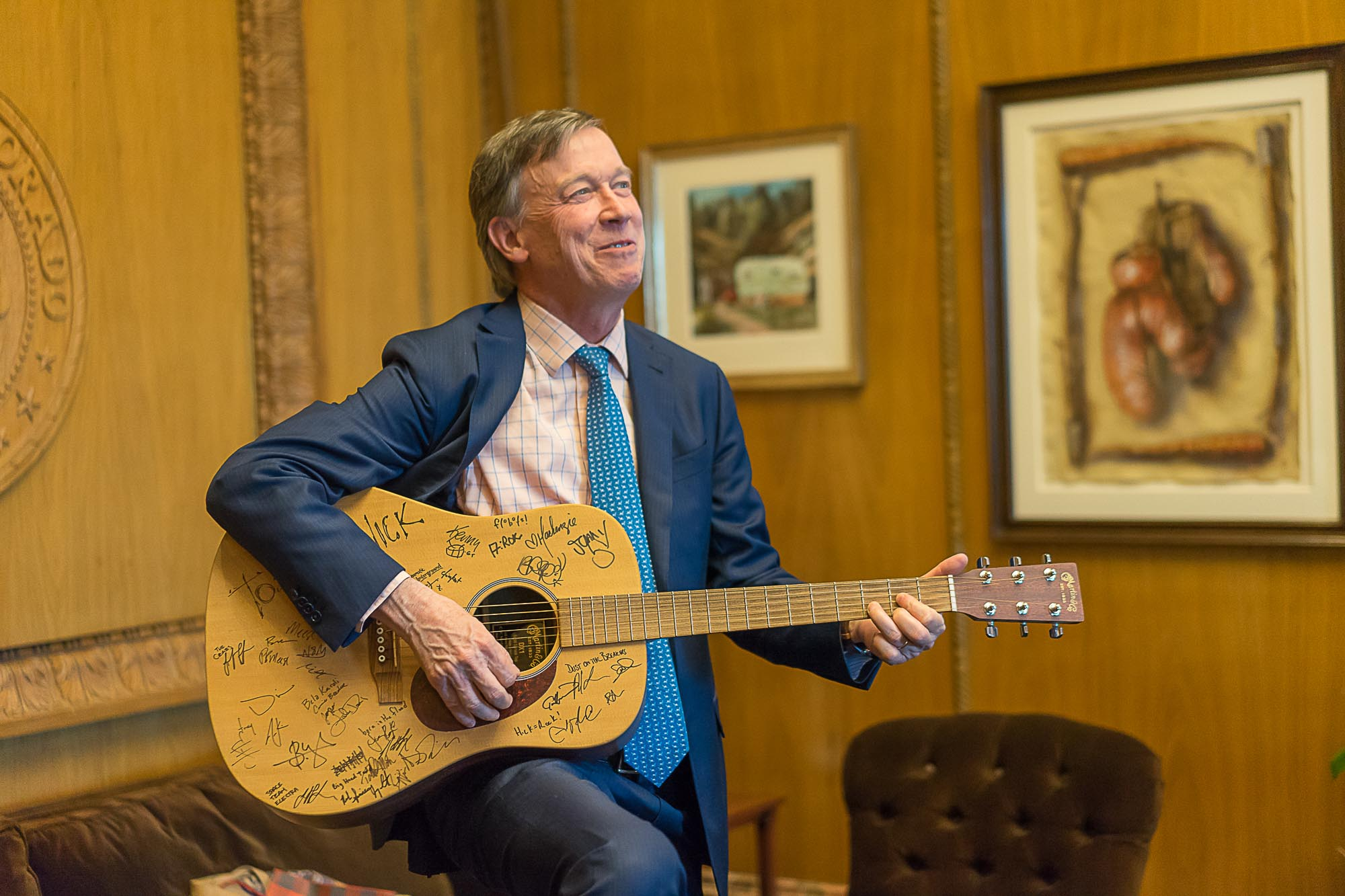 The Governor of Colorado plays a guitar in Denver.