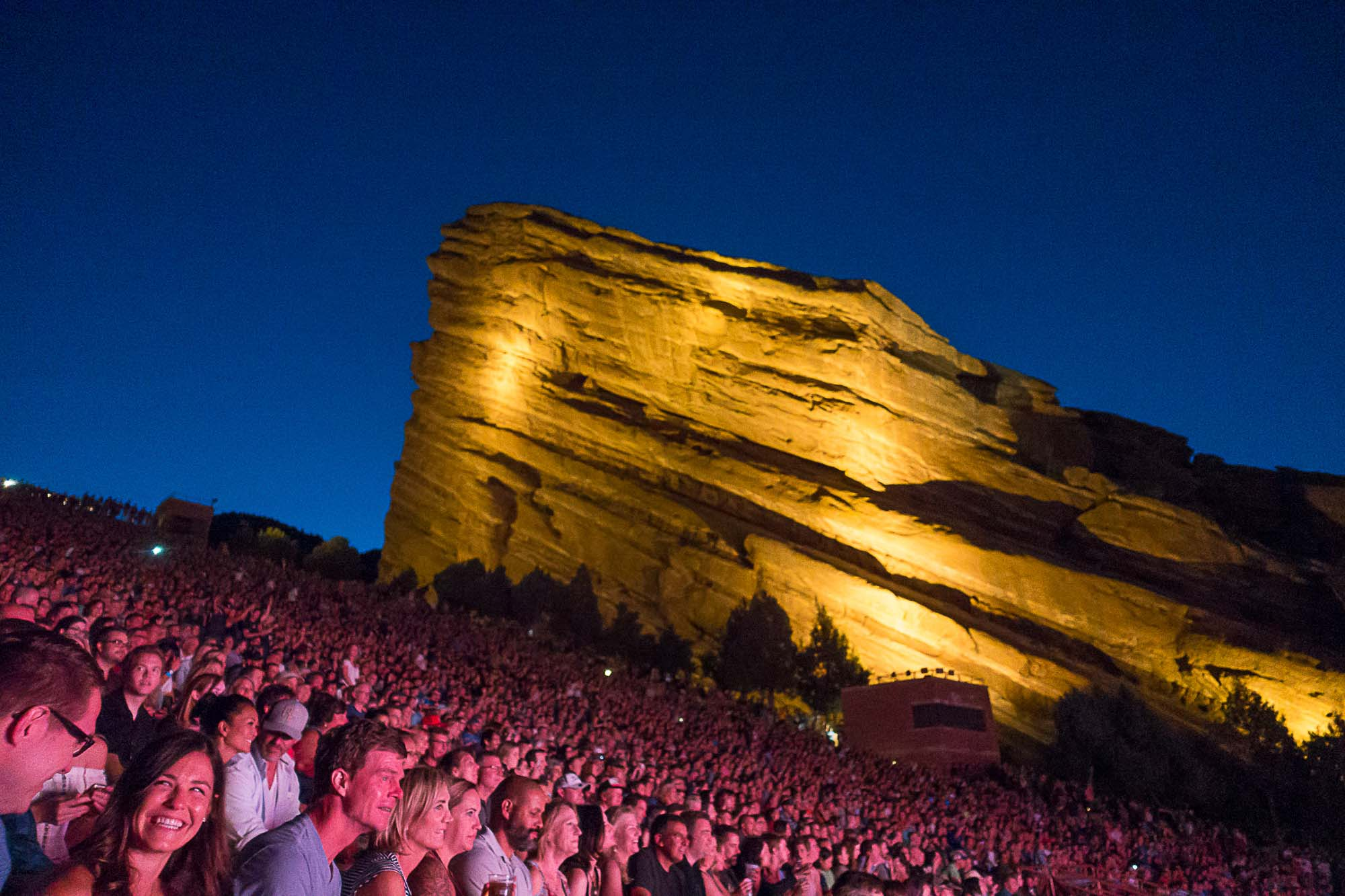 Crowd watches a show at night at Red Rocks.