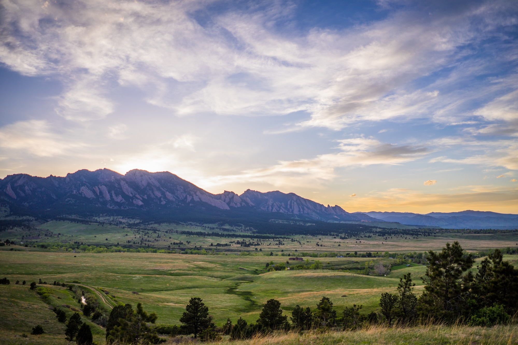 sunset behind the Flatirons with a creek snaking through a green field