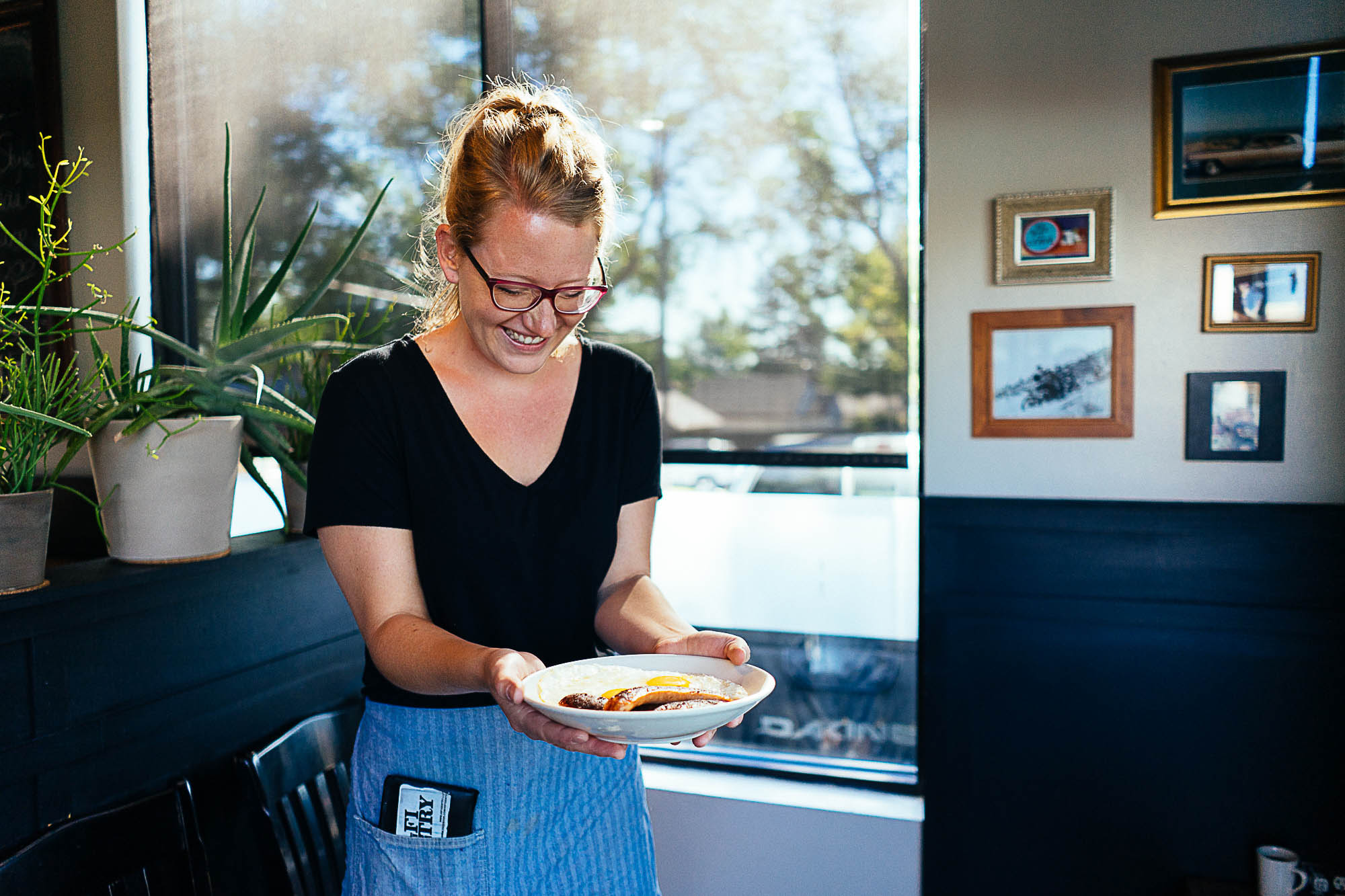 A waitress holds a plate of food at The Universal Denver.