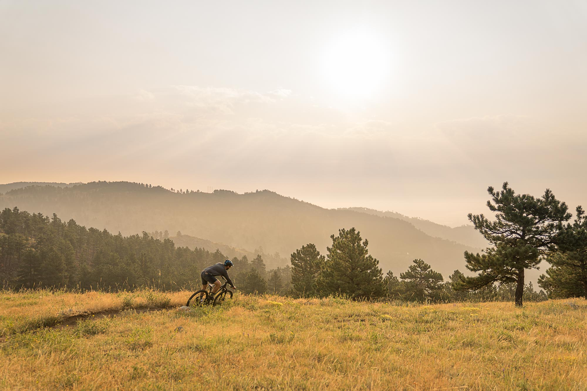 A mountain biker riding through Betasso Preserve as the sunrises in Boulder, Colorado.