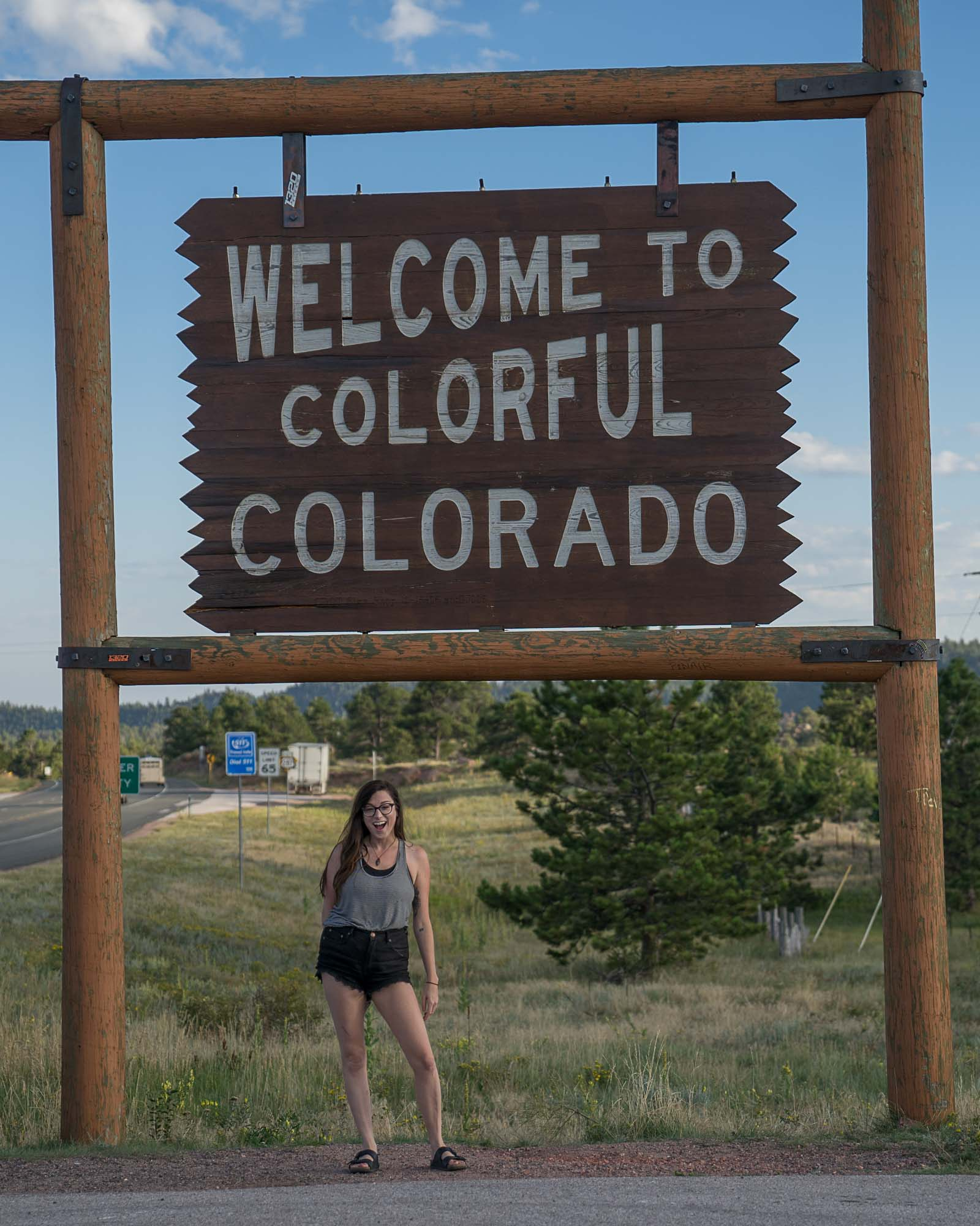 Jess hangs out in front of the Welcome to Colorado sign at the border of Wyoming and Colorado.