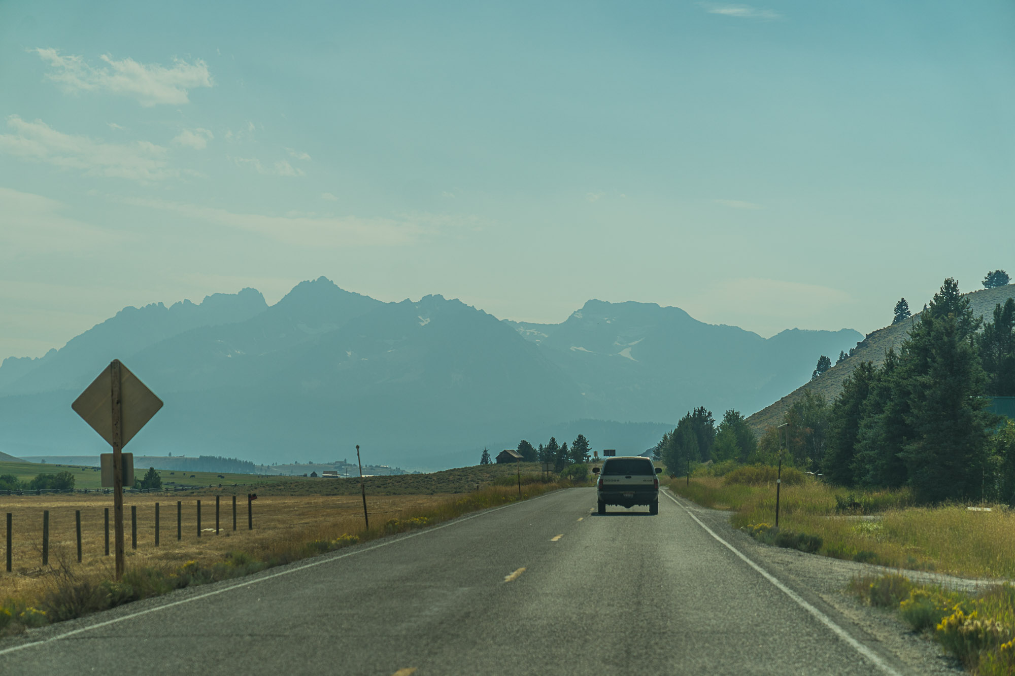 A car drives towards the Sawtooth Mountains on the road into town of Stanley, Idaho.