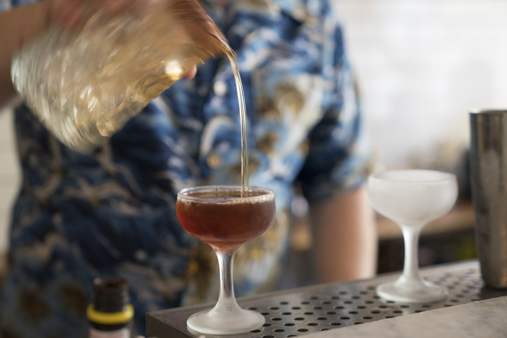 A bartender pours a drink at Essex in Seattle.