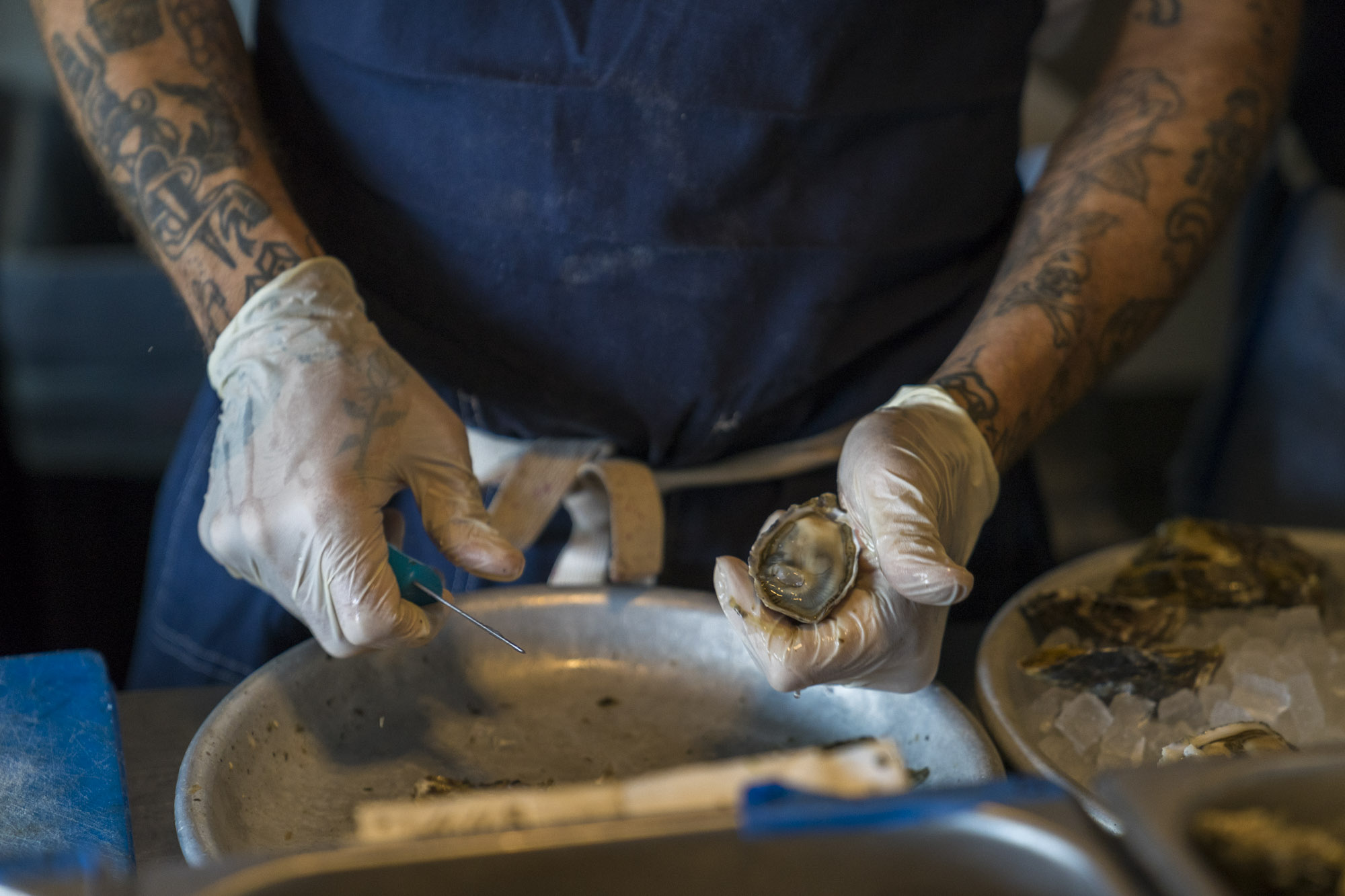 A close-up of a guy with tattoos shucking oysters in Seattle.