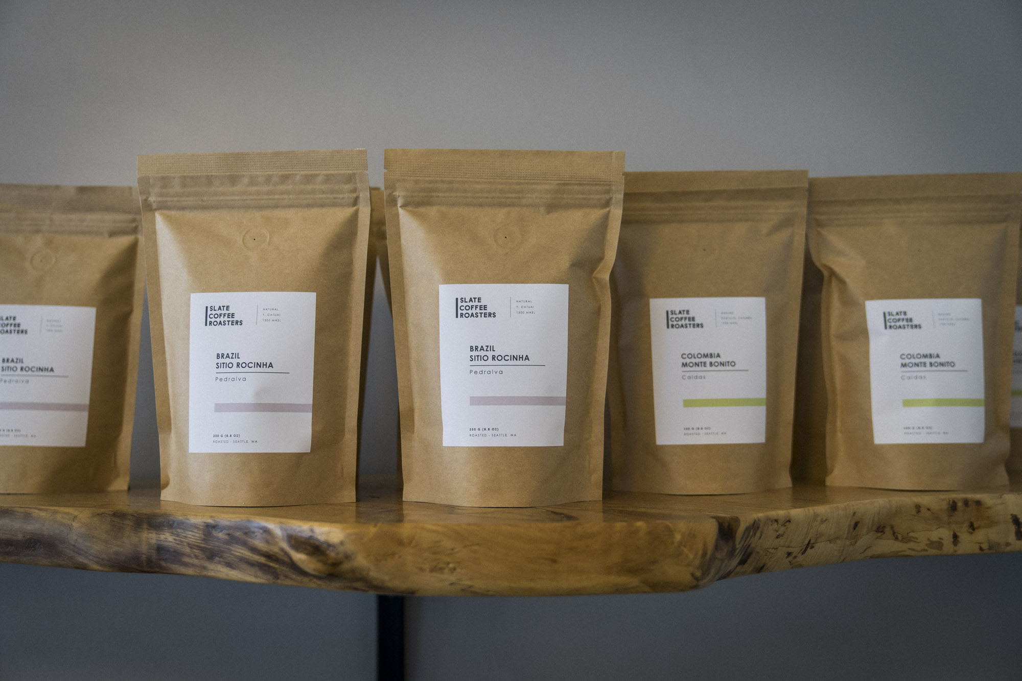 Slate Coffee Roasters packaging on a wood shelf against a wall.