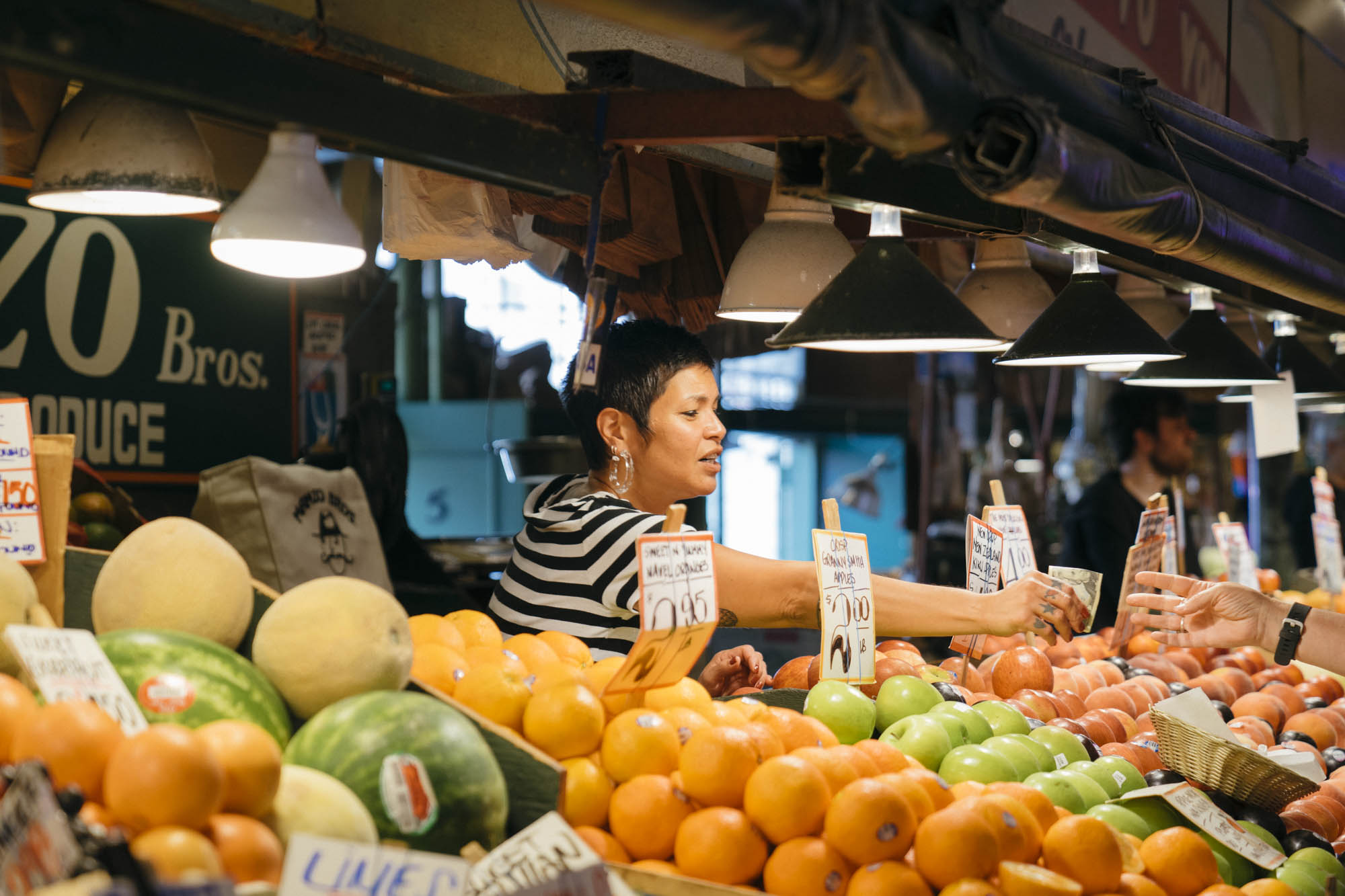 Woman holds oranges at Pike Place in Seattle.