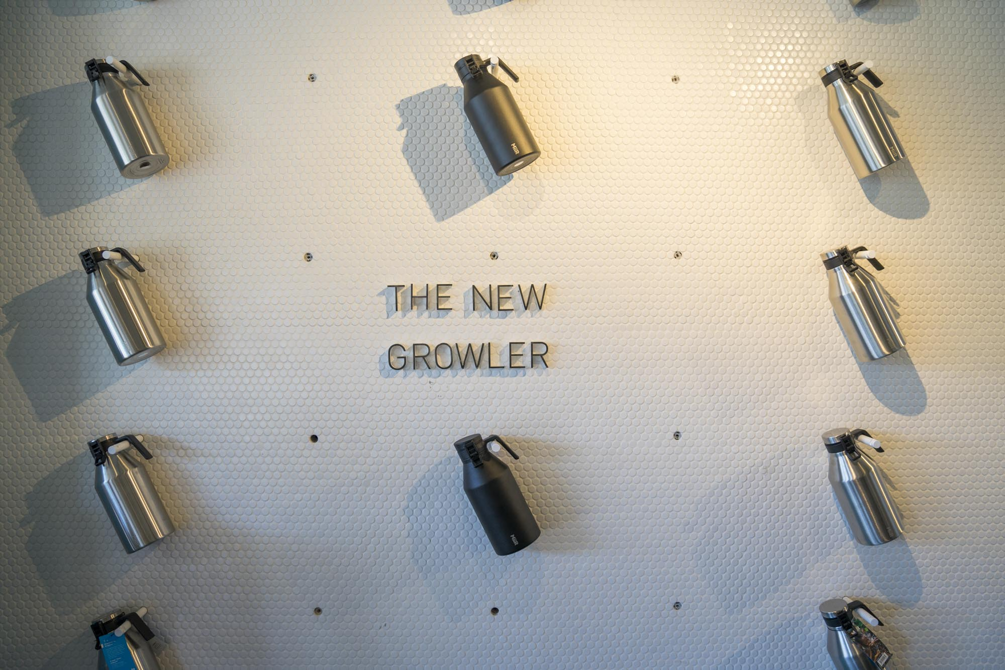 MiiR's growlers hanging on a wall at Miir Flagship in Seattle.