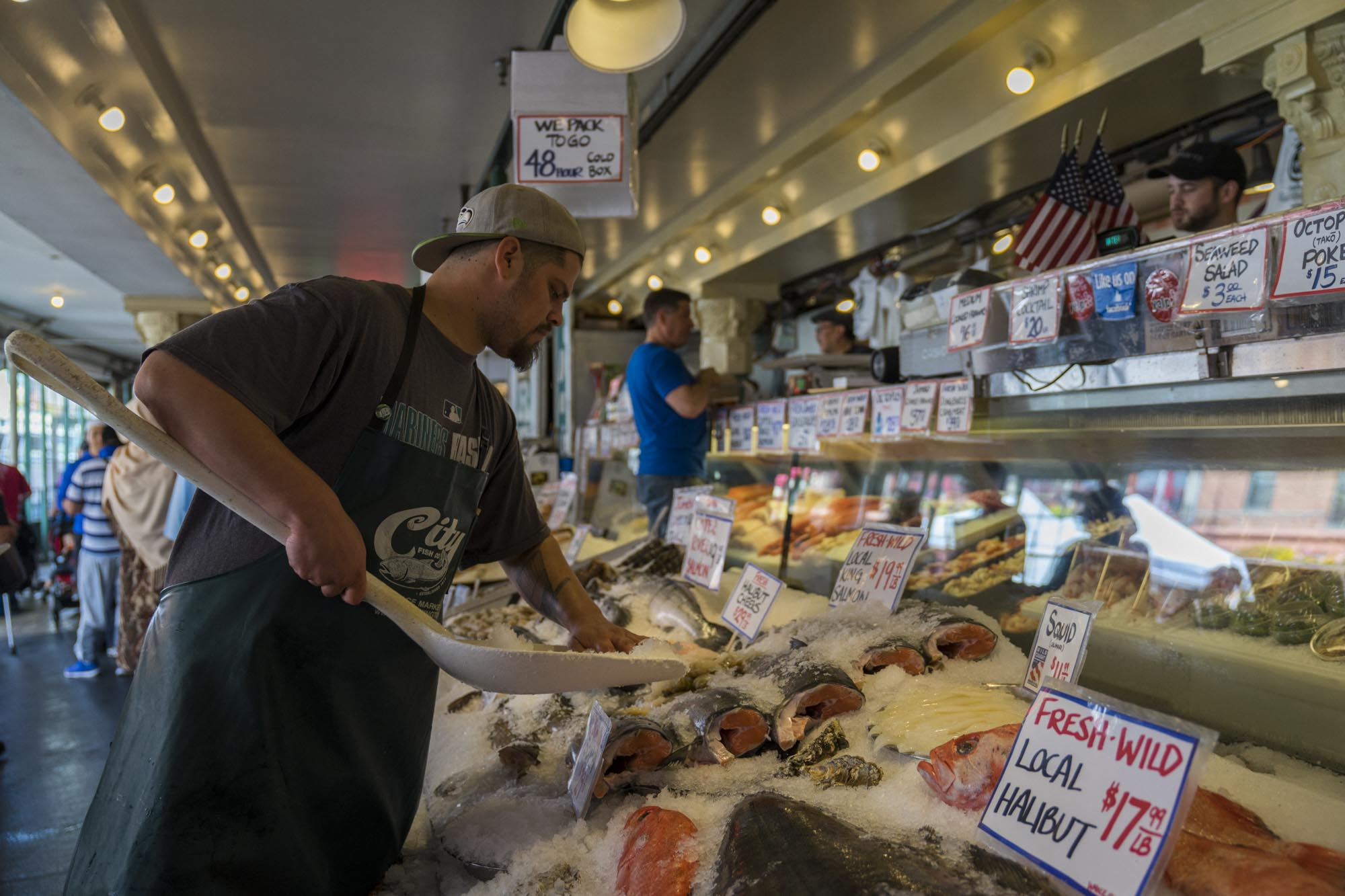 Man puts ice on top of fresh fish at Pike's Place.