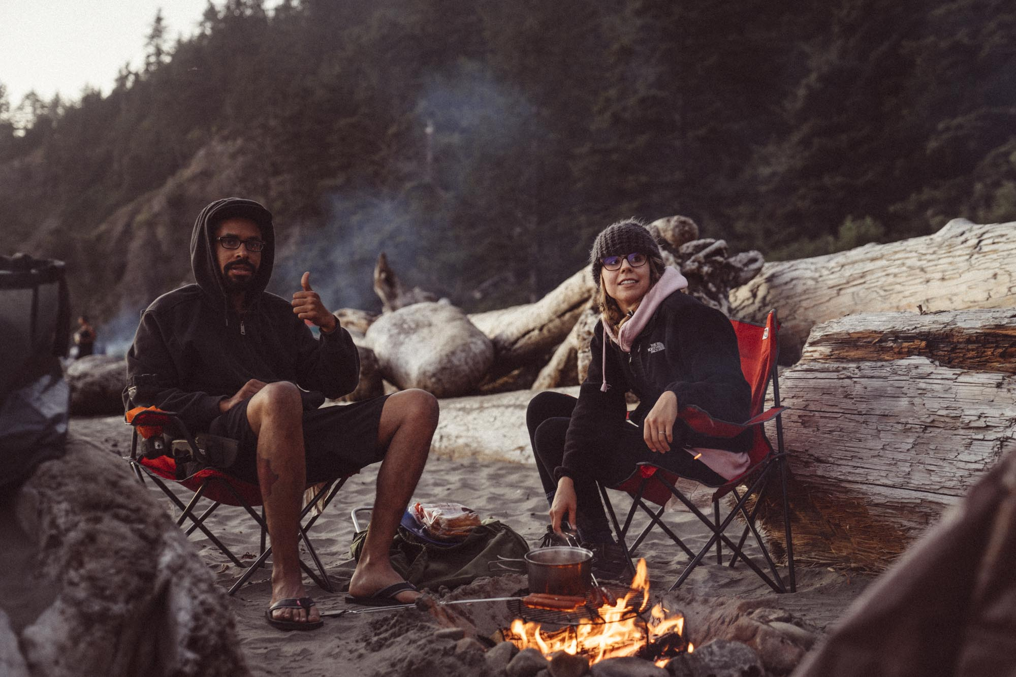 Couple sits at a campfire at Second Beach in Olympic National Park.