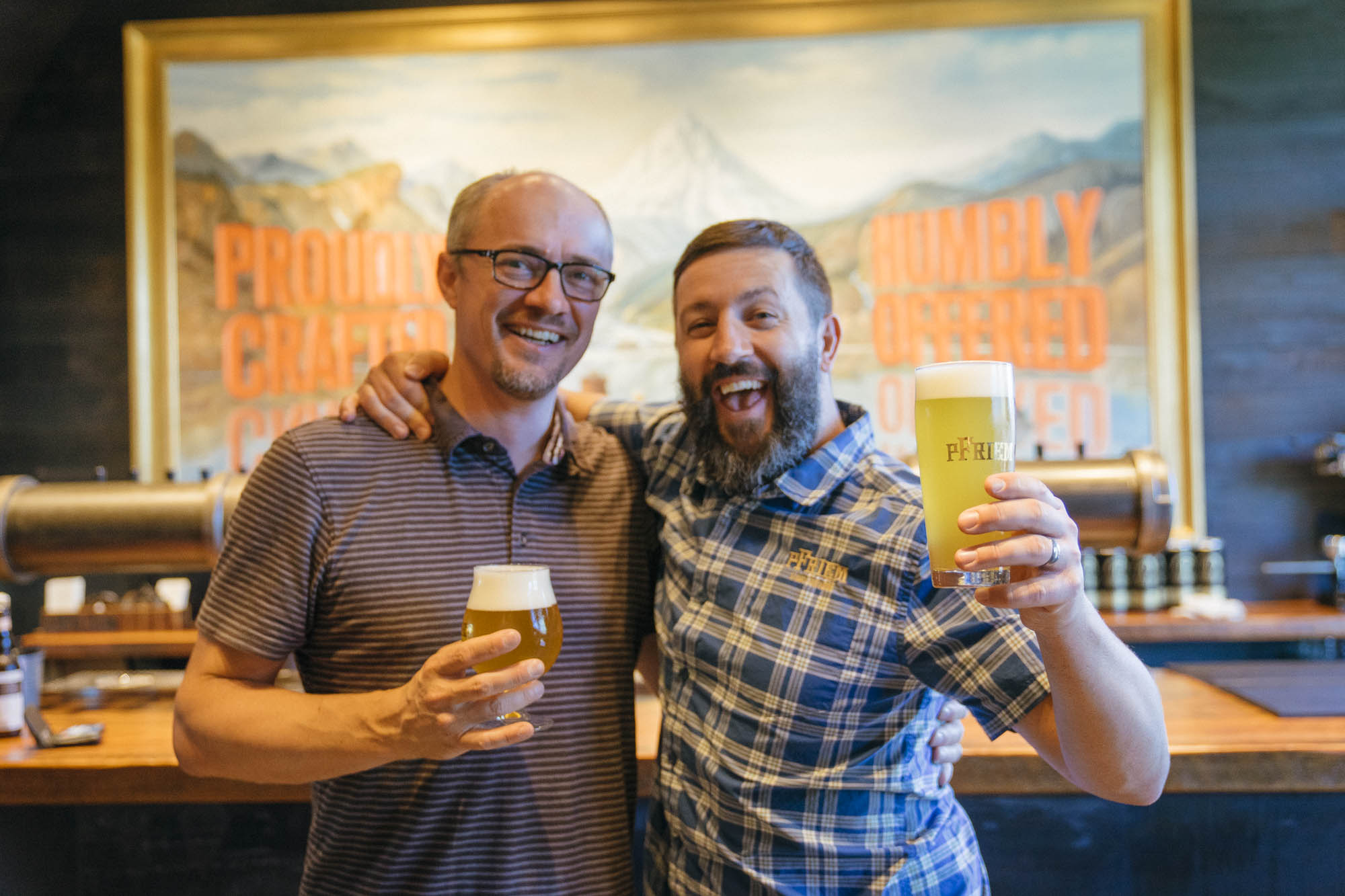 The owners of pFriem Family Brewers celebrate and smile with beers in their taproom in Hood River, Oregon.