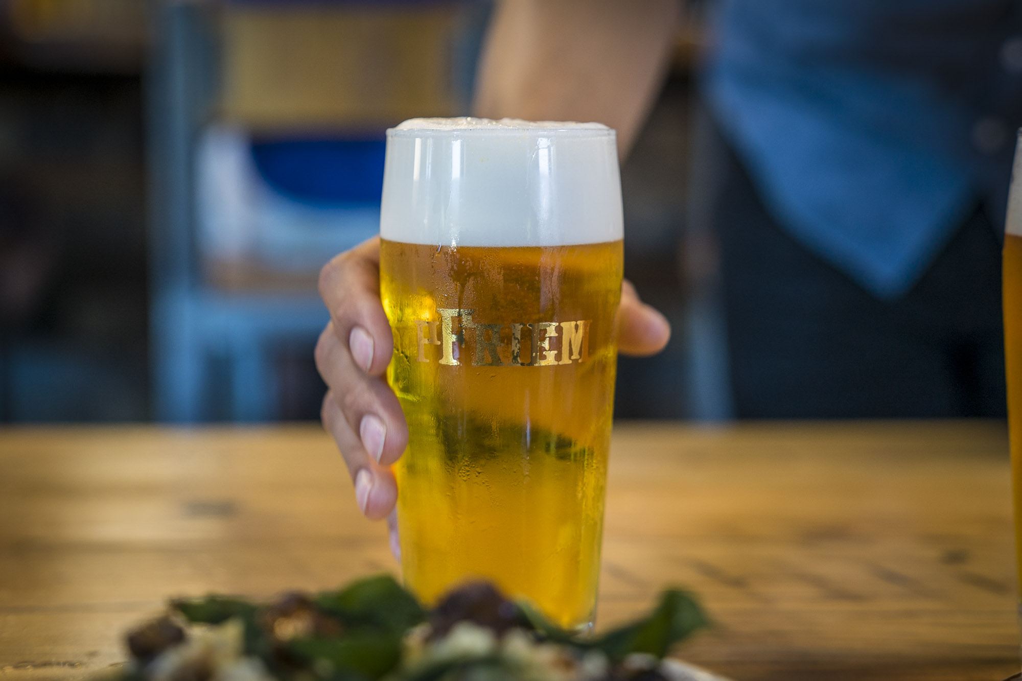 A woman holds a beer at pFriem Family Brewers in Hood River, Oregon for Dirt Road Travels.