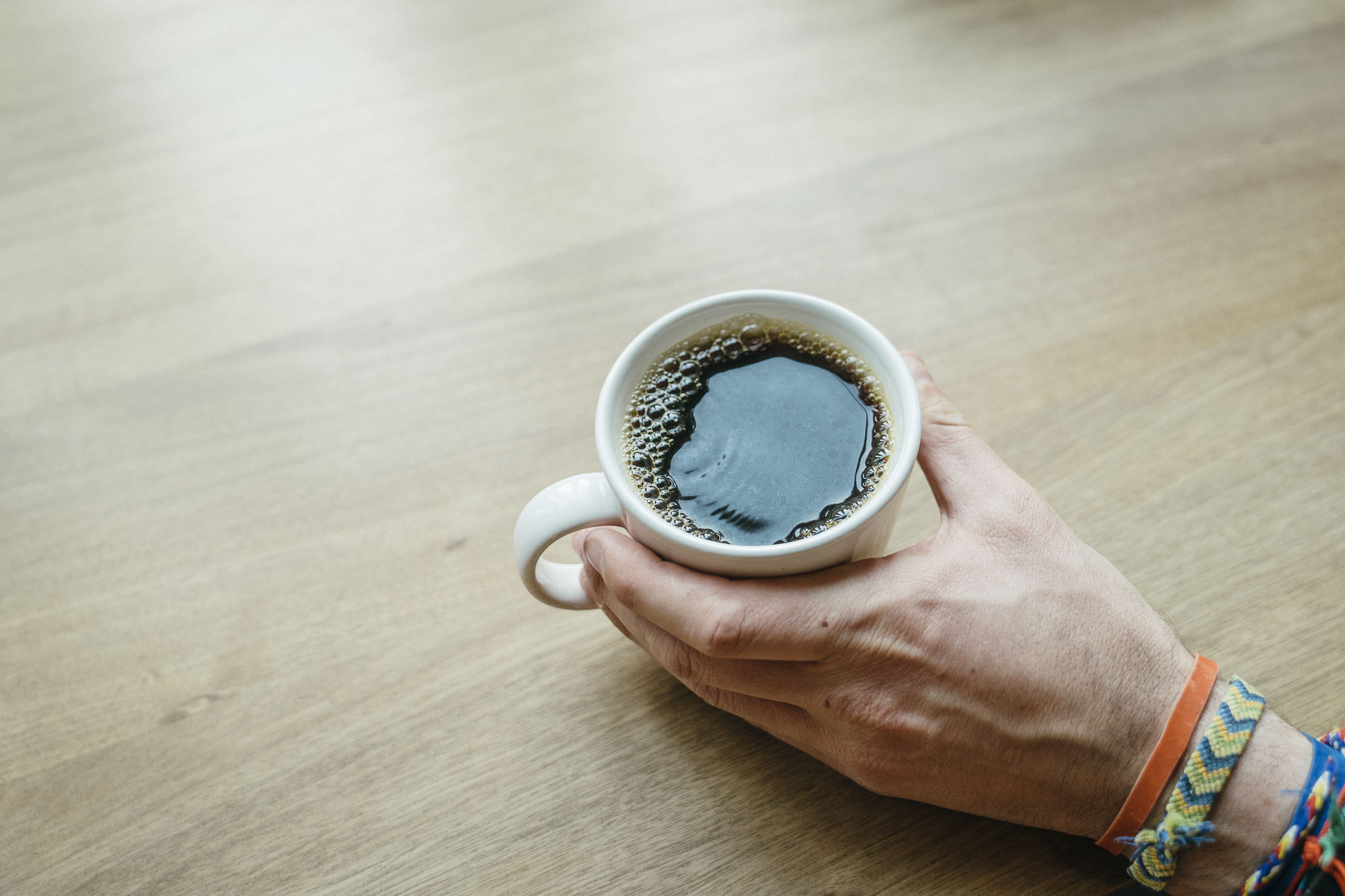 A hand holding a cup of coffee at Heart in Portland for Dirt Road Travels