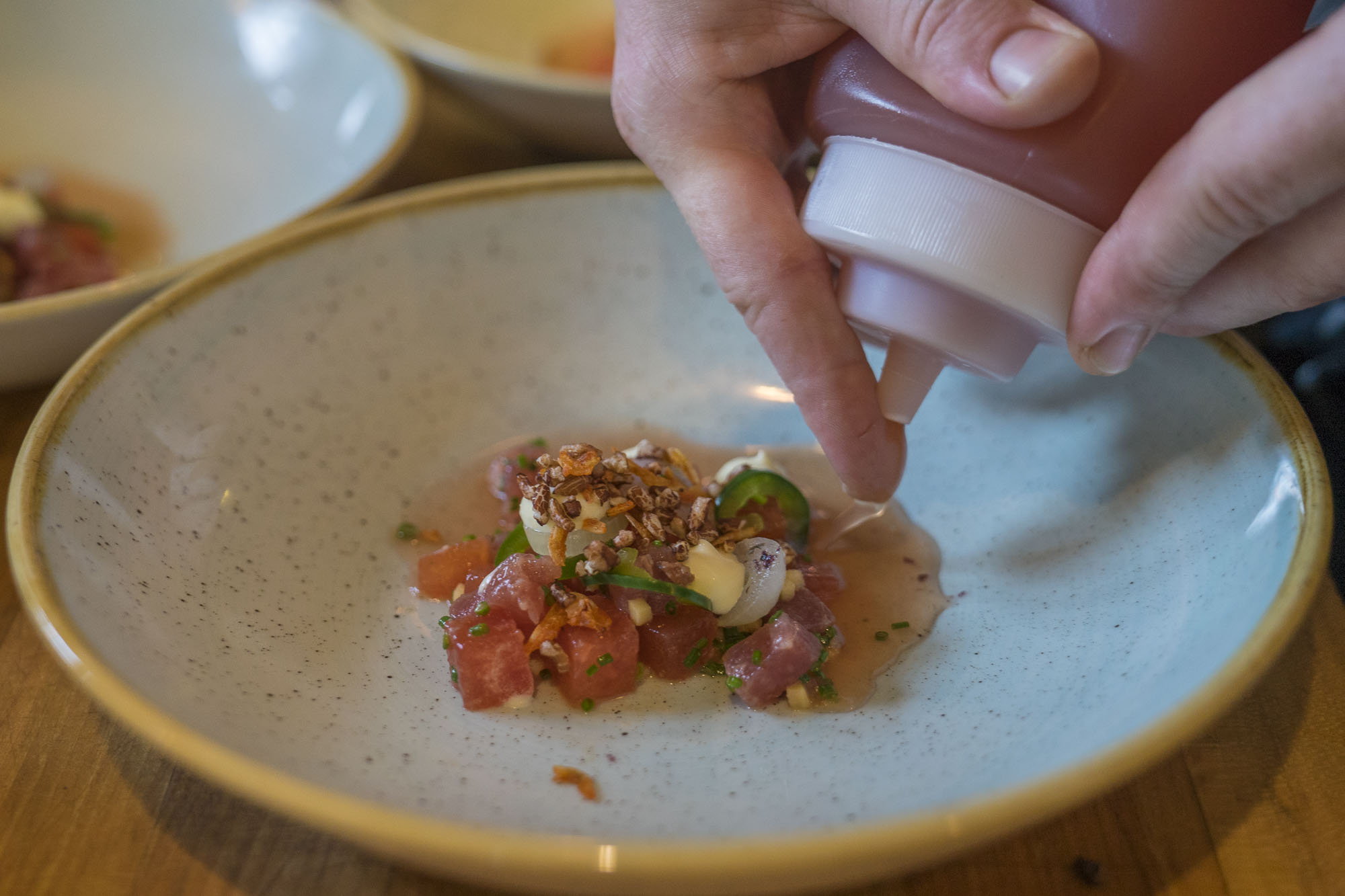 hand drizziling sauce on top of finished dish