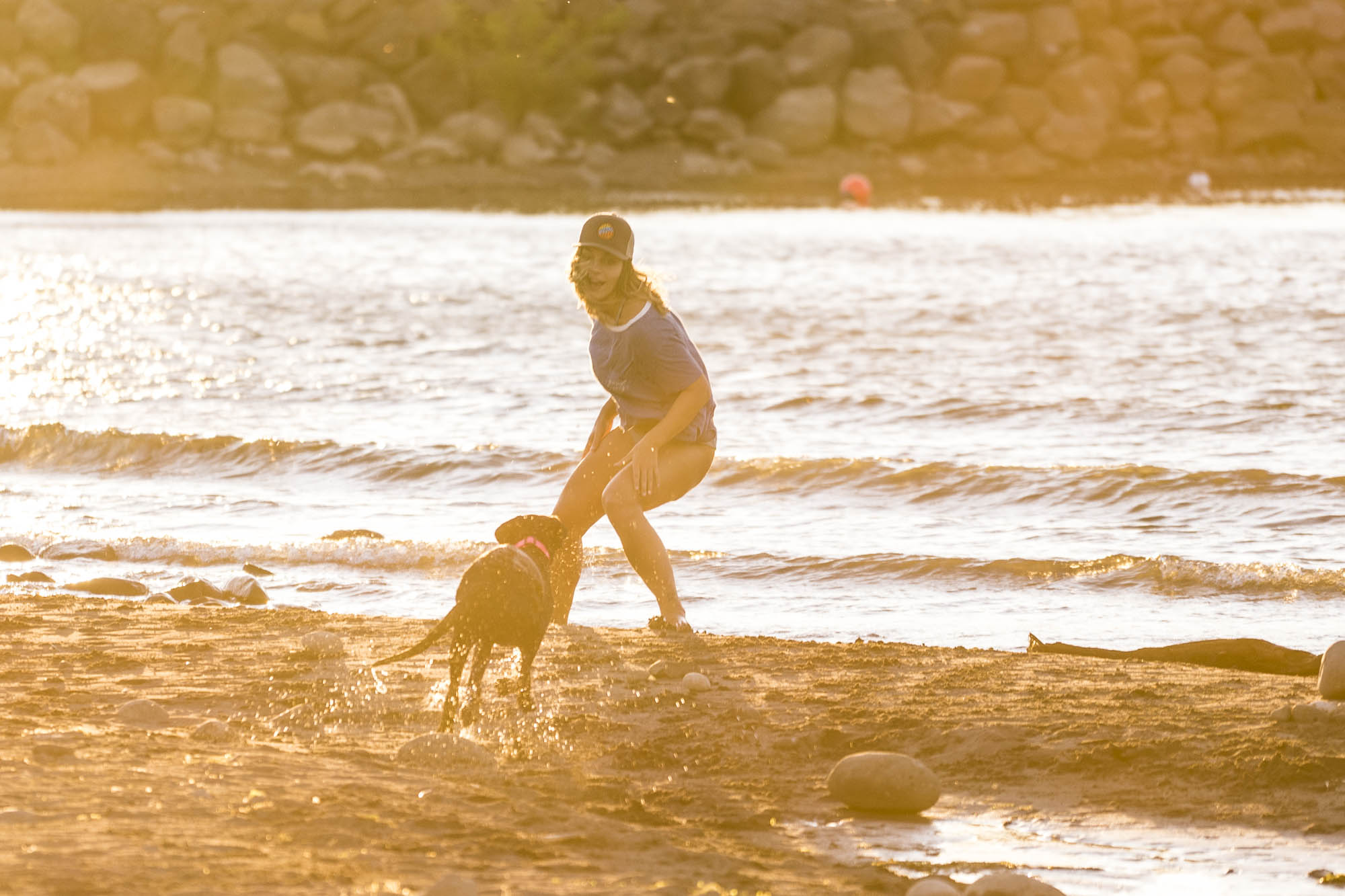 A woman plays with a dog on the Columbia River in Hood River, OR.