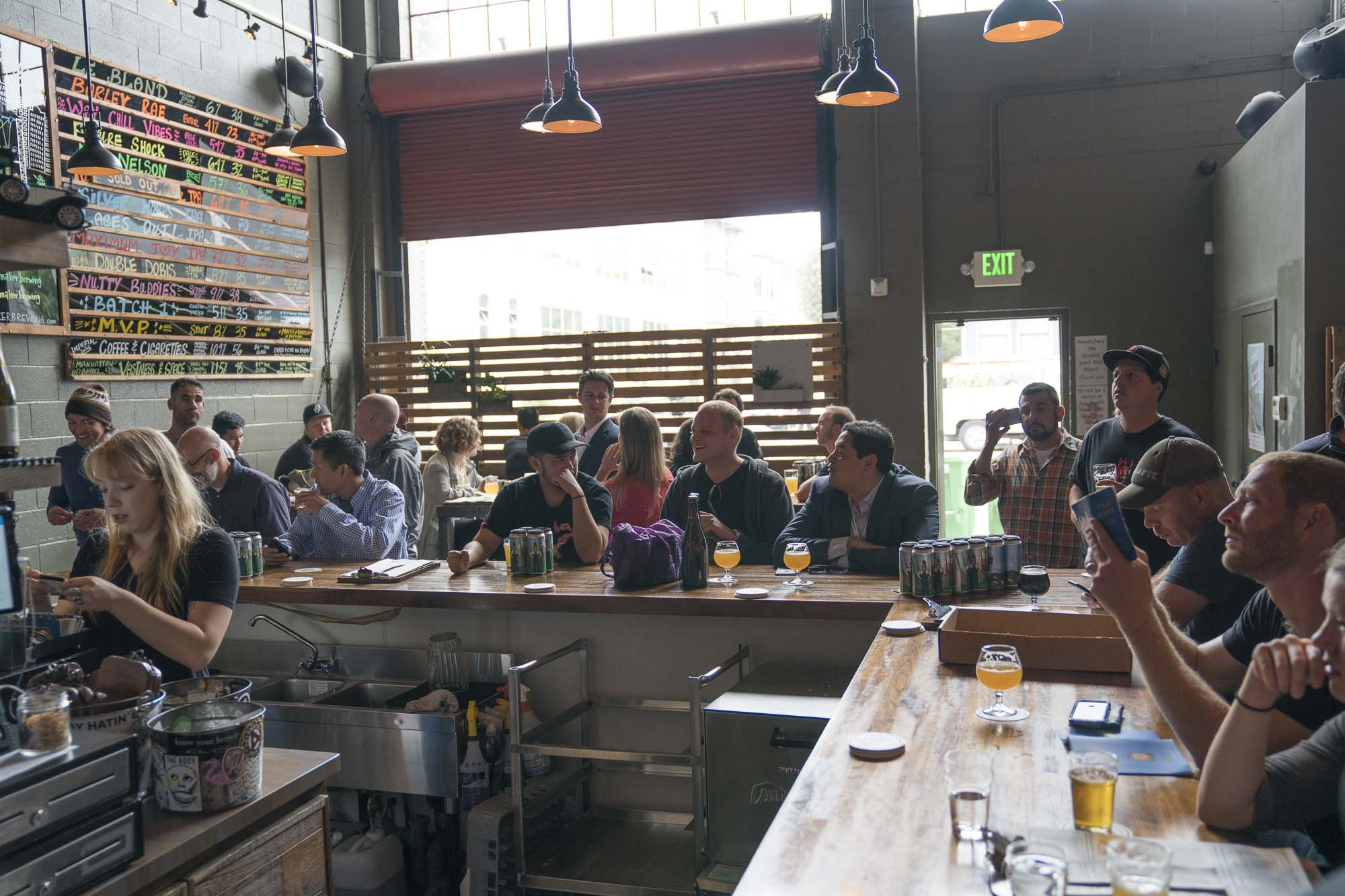 People sit around the bar drinking beer at Cellarmaker Brewery in San Francisco, California for Dirt Road Travels