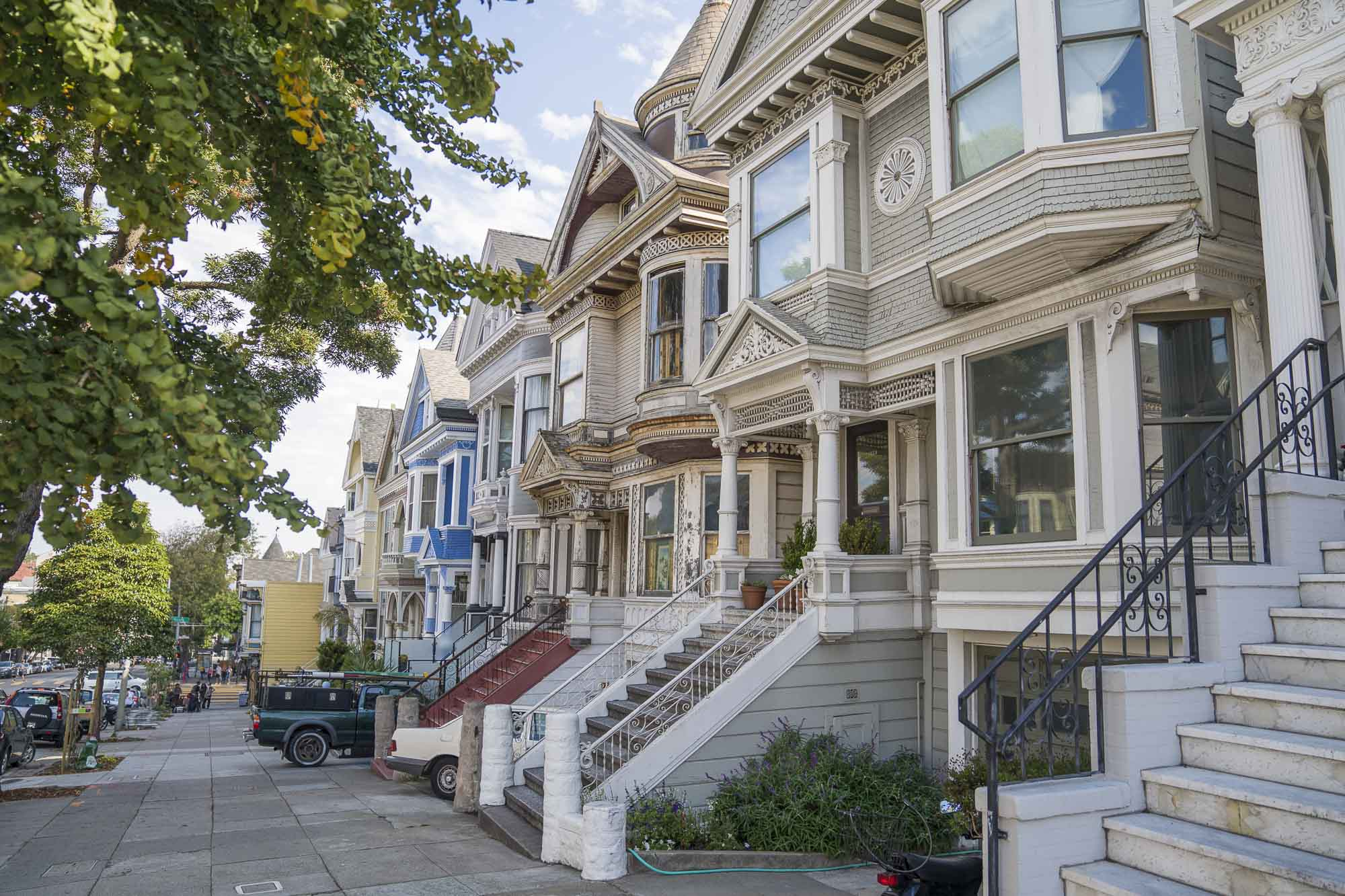 colorful san francisco homes lined along the sidewalk