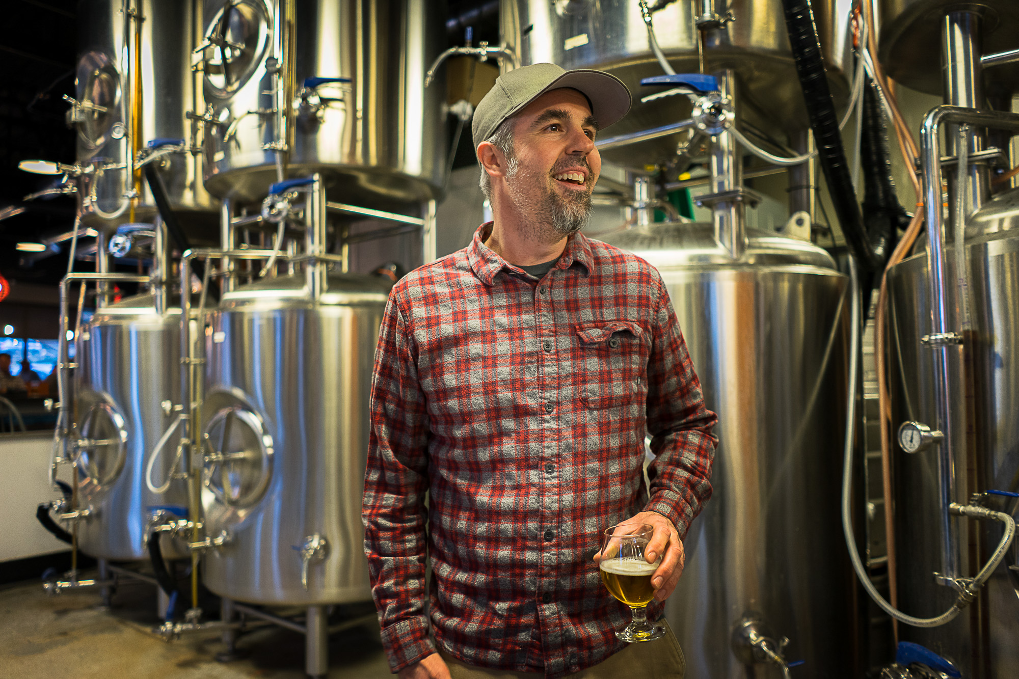 The owner of Cannonball Creek Brewing in Denver, Colorado stands holding his beer for Dirt Road Travels
