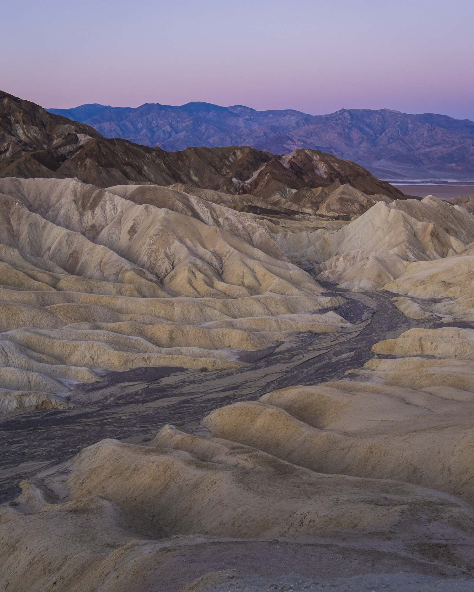 the view of distant mountains from Zabriskie point in Death valley california for dirt road travels