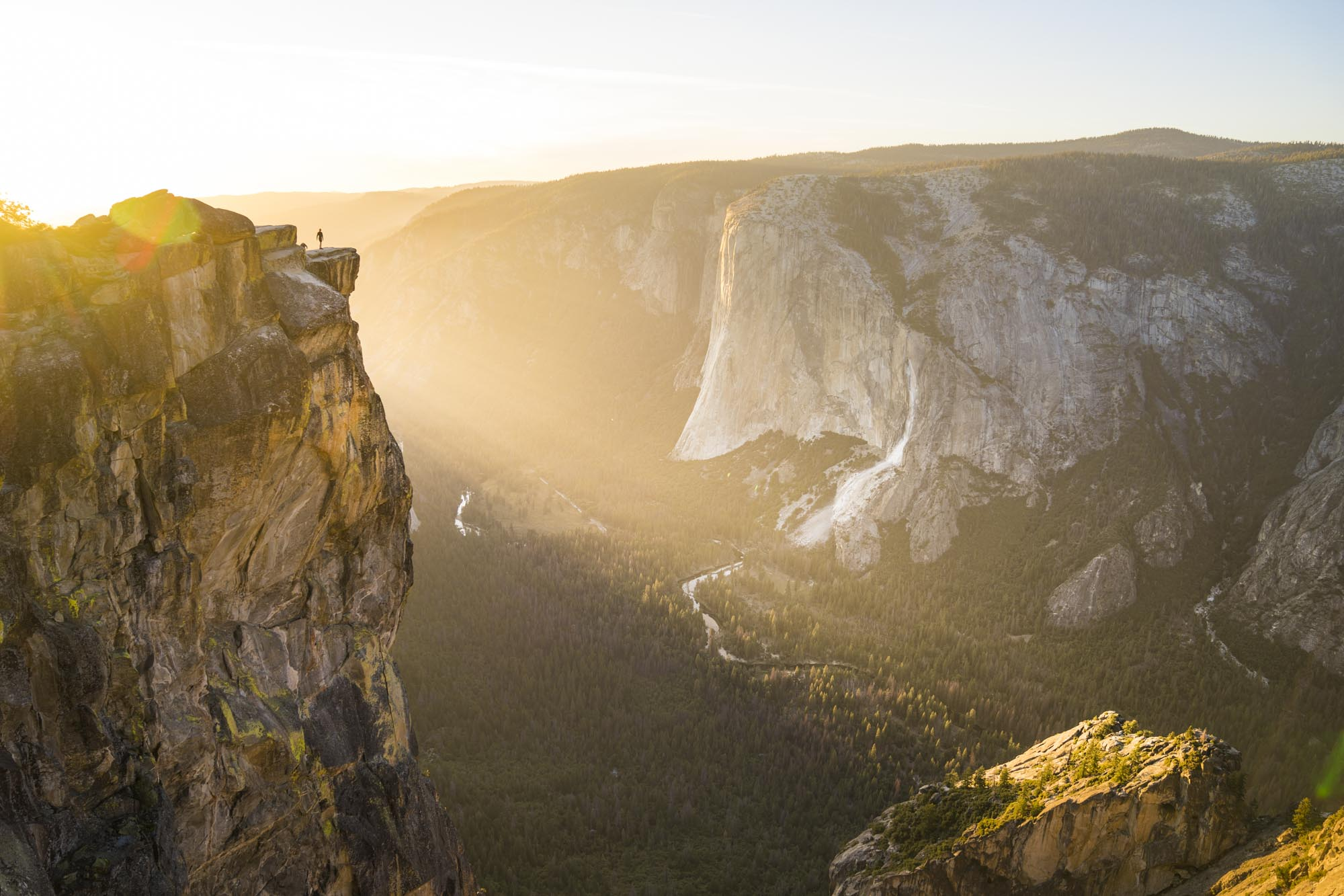 a figure stands on a cliff on taft point in yosemite national park for dirt road travels