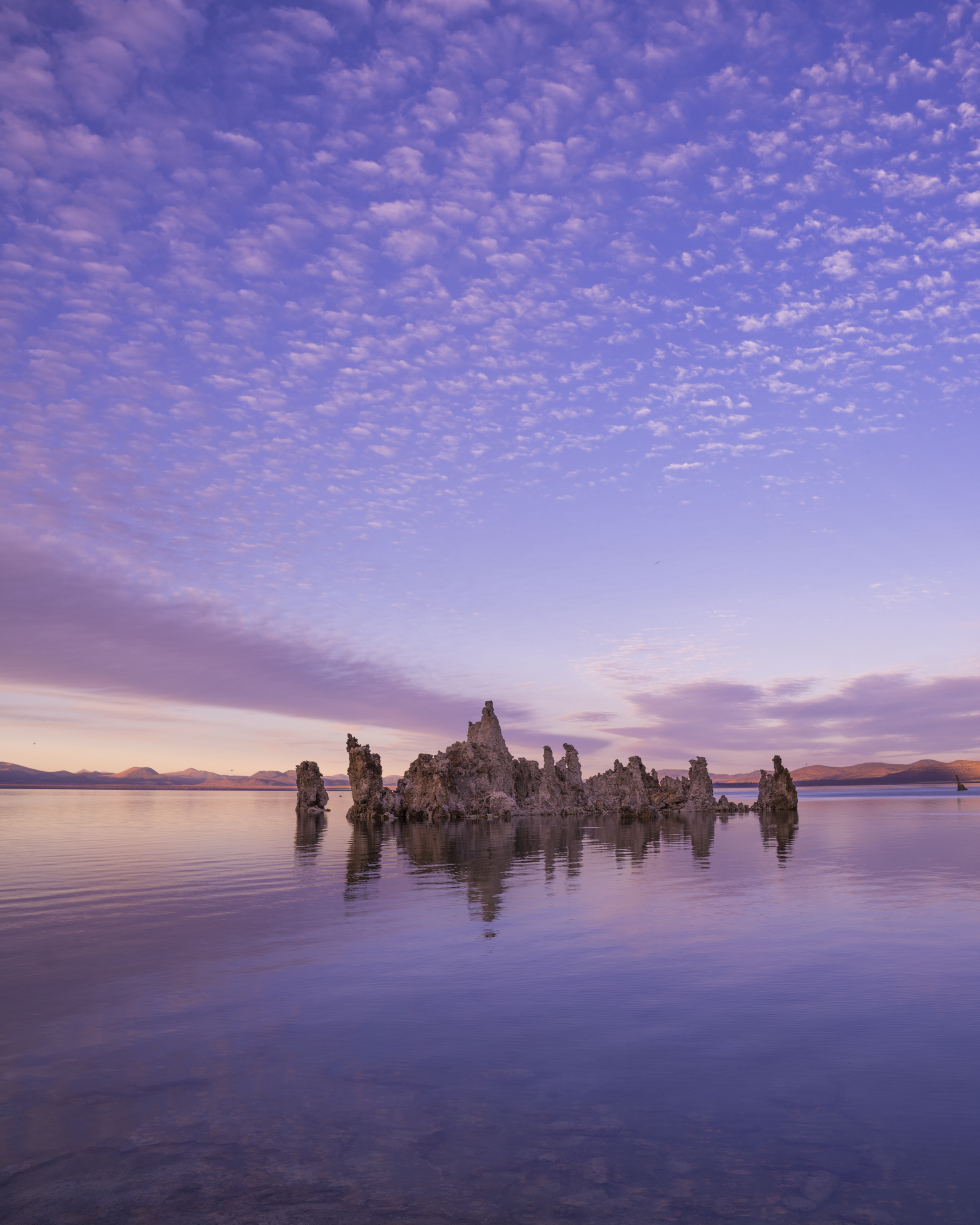 a rock formation in mono lake against a purple sunset backdrop for dirt road travels