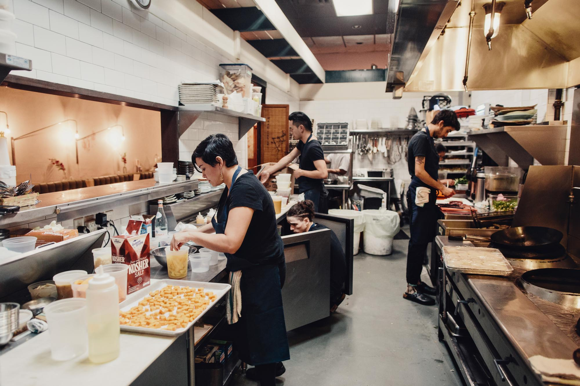 Chefs prepare meals in the kitchen of Bao Bei in Vancouver, British Columbia as part of the Dirt Road Travels city guide.