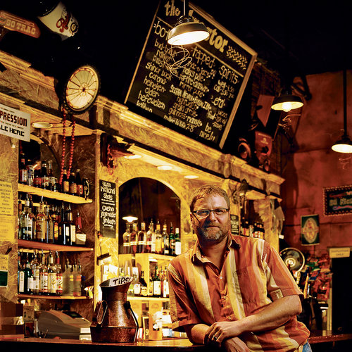 Owner of Tractor Tavern leaning on bar with bottles lining the shelves behind him.