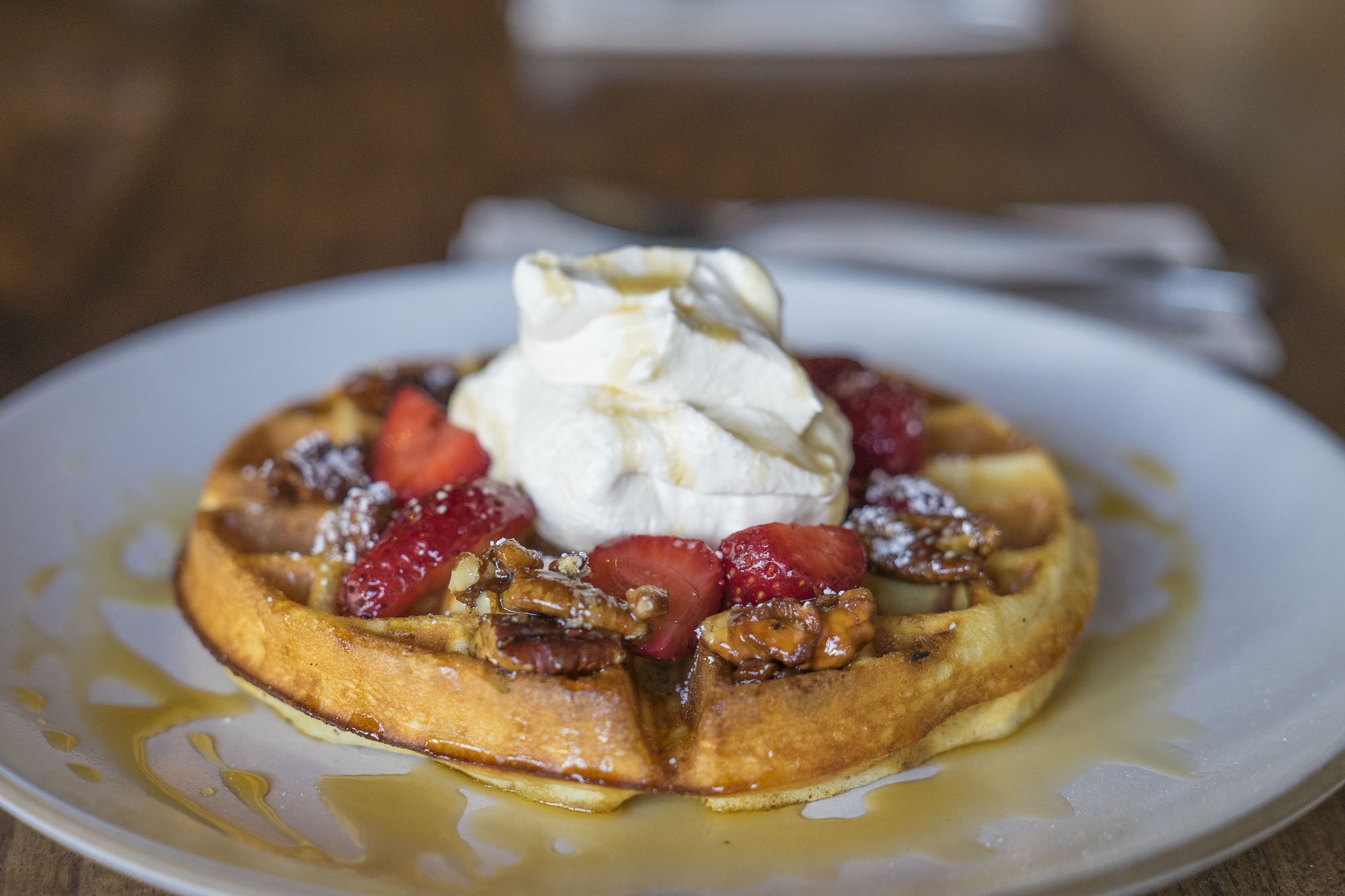 waffle with whipped cream, strawberries, pecans and syrup