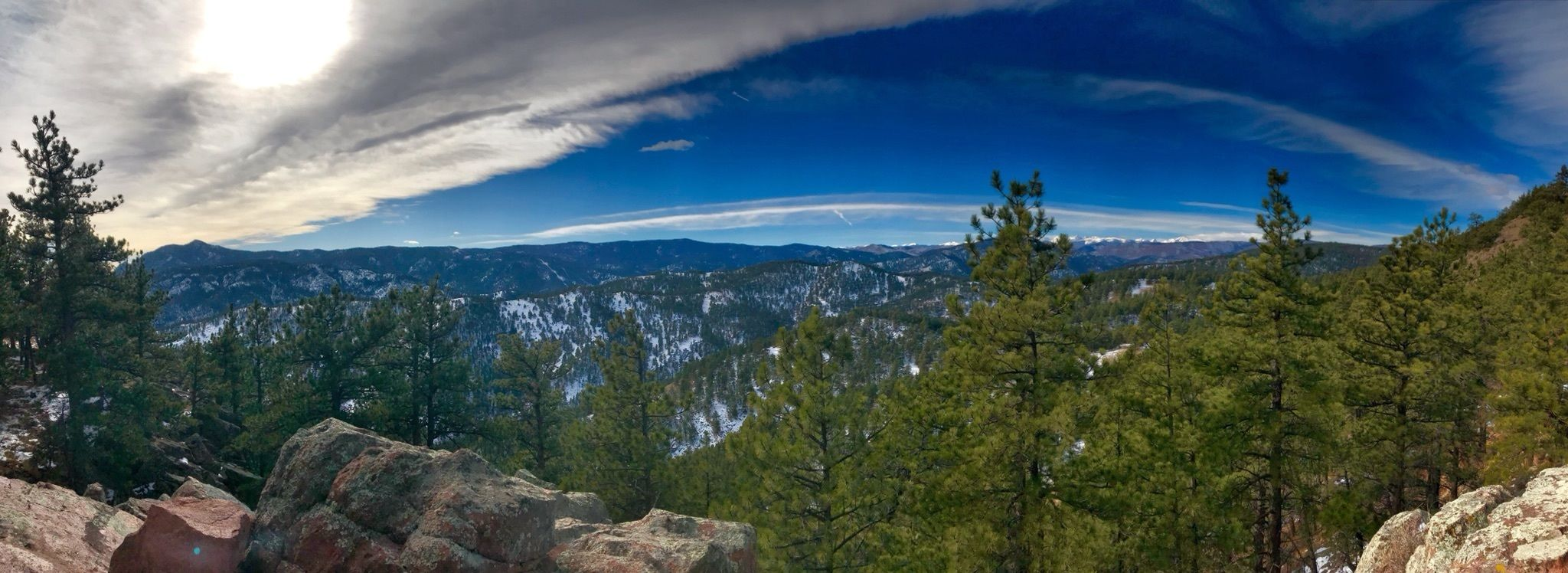 panoramic view from the Mount Sanitas Trail, blue skies, green trees and mountains in the background