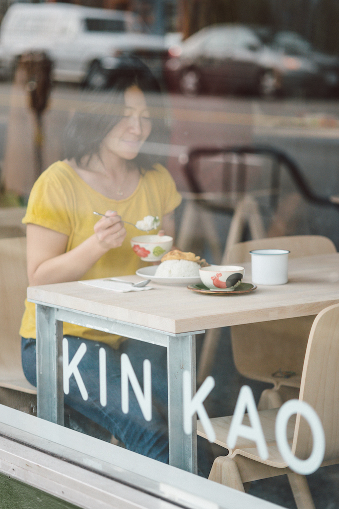 Woman eating dinner at Kin Kao in Vancouver, British Columbia as part of the Dirt Road Travels city guide.