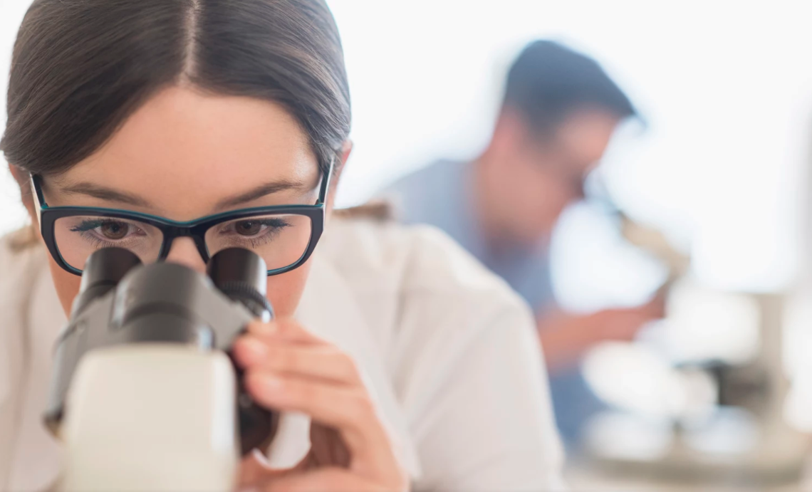 Cientista observadora microscopio