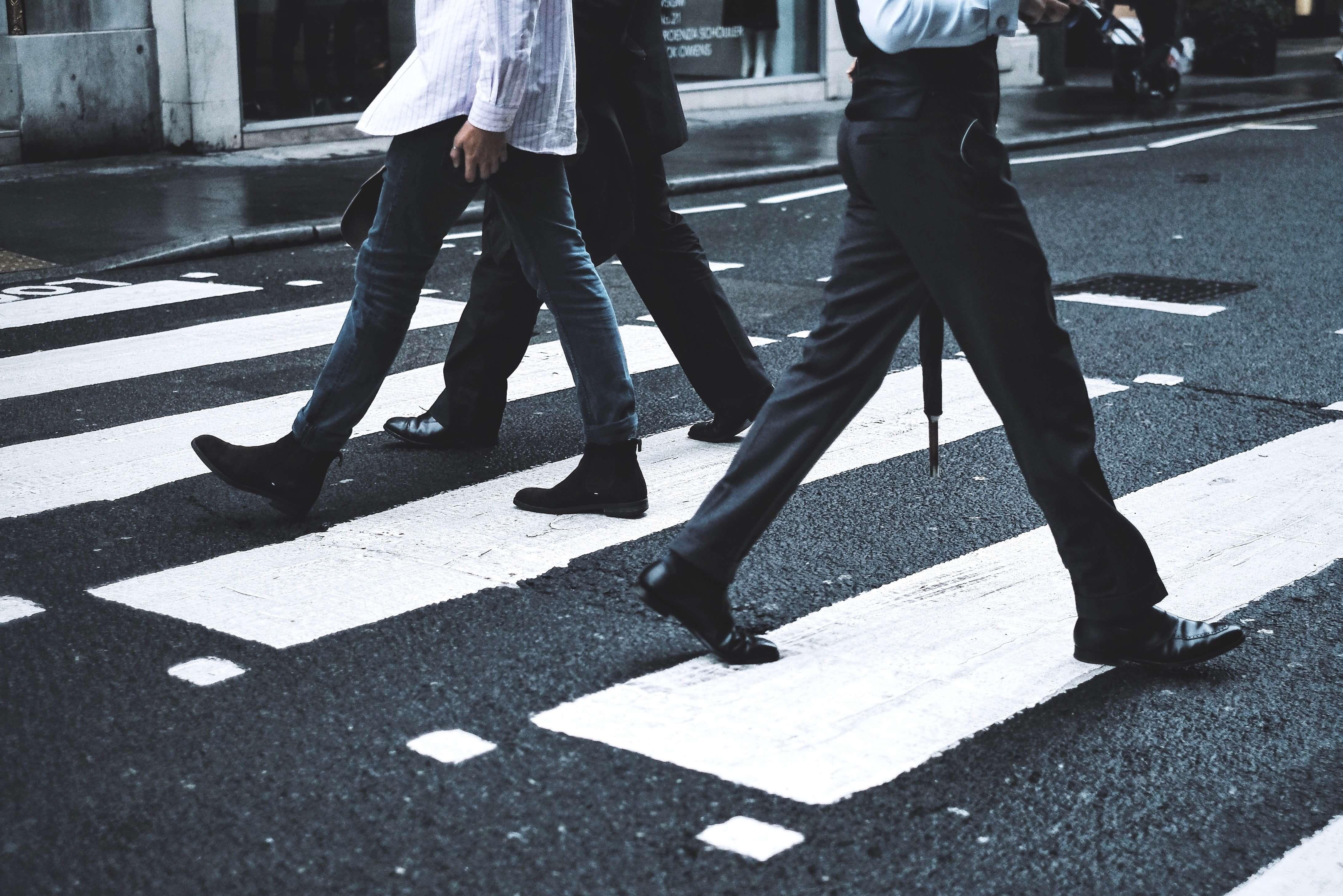Pessoas caminhando pela faixa de pedestres