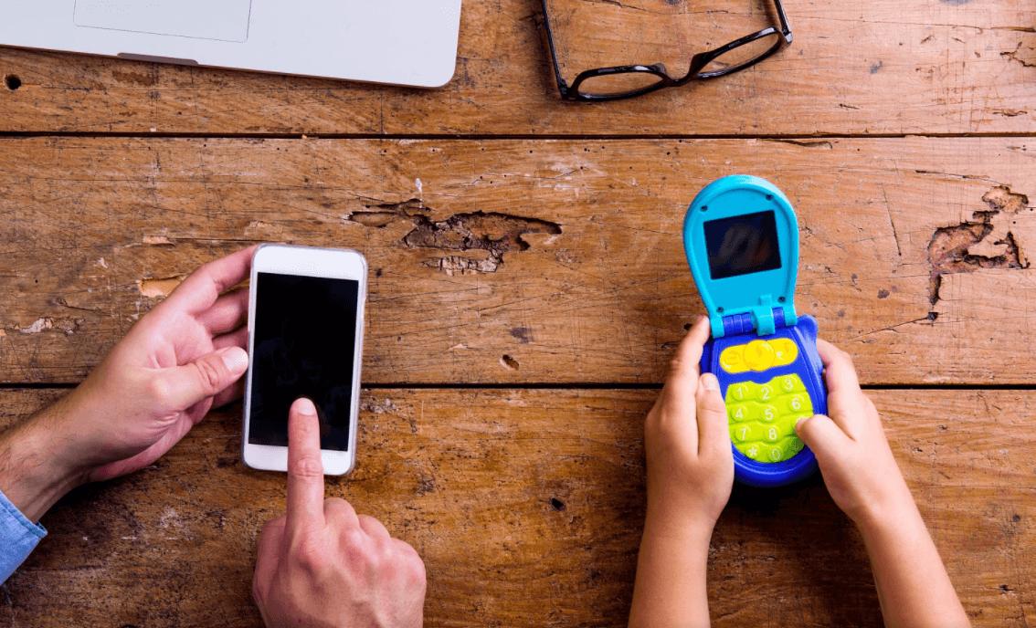Criança e adulto mexendo em seus celulares