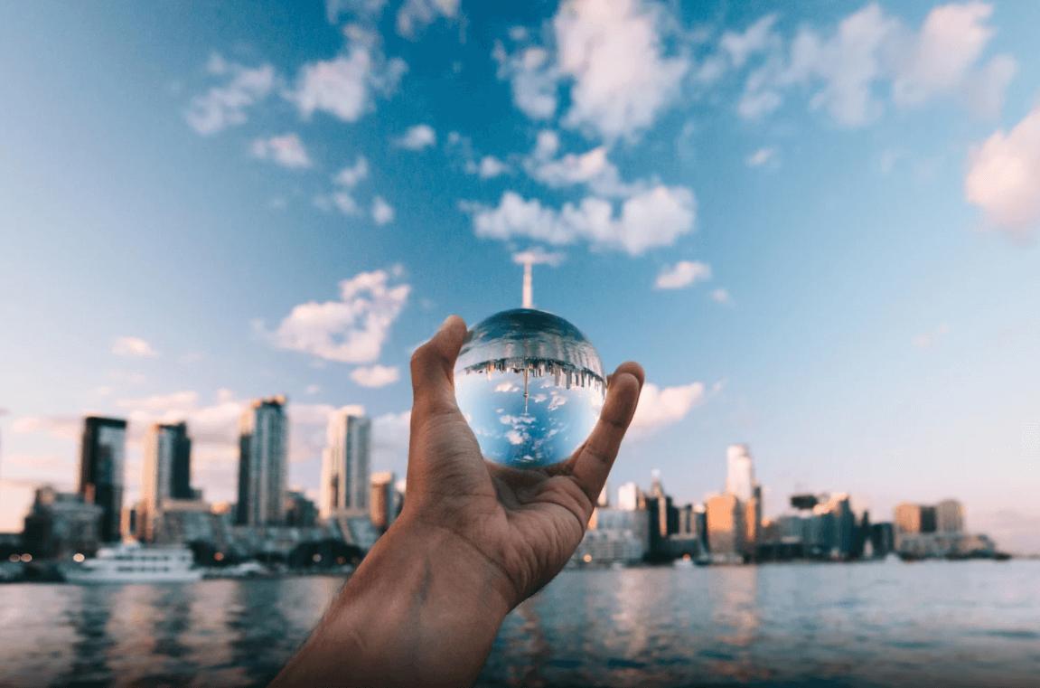 Bola de cristal sendo segurada em frente a cidade