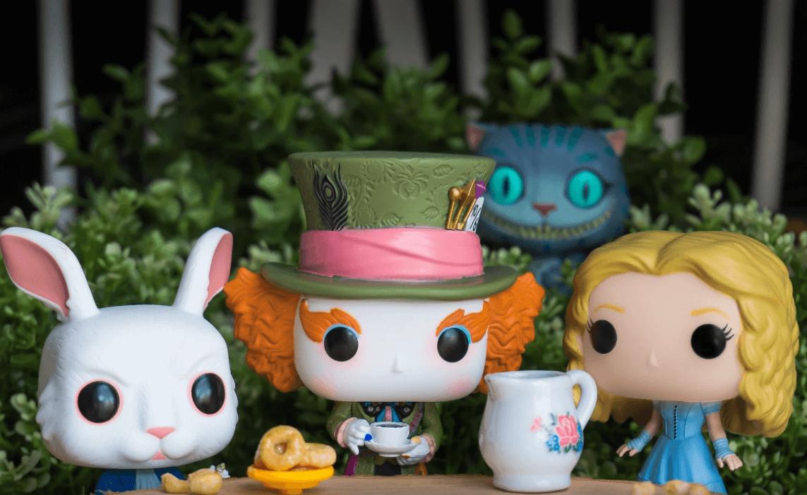 Alice, Chapeleiro Maluco, Coelho branco e Gato Risonho tomando chá.