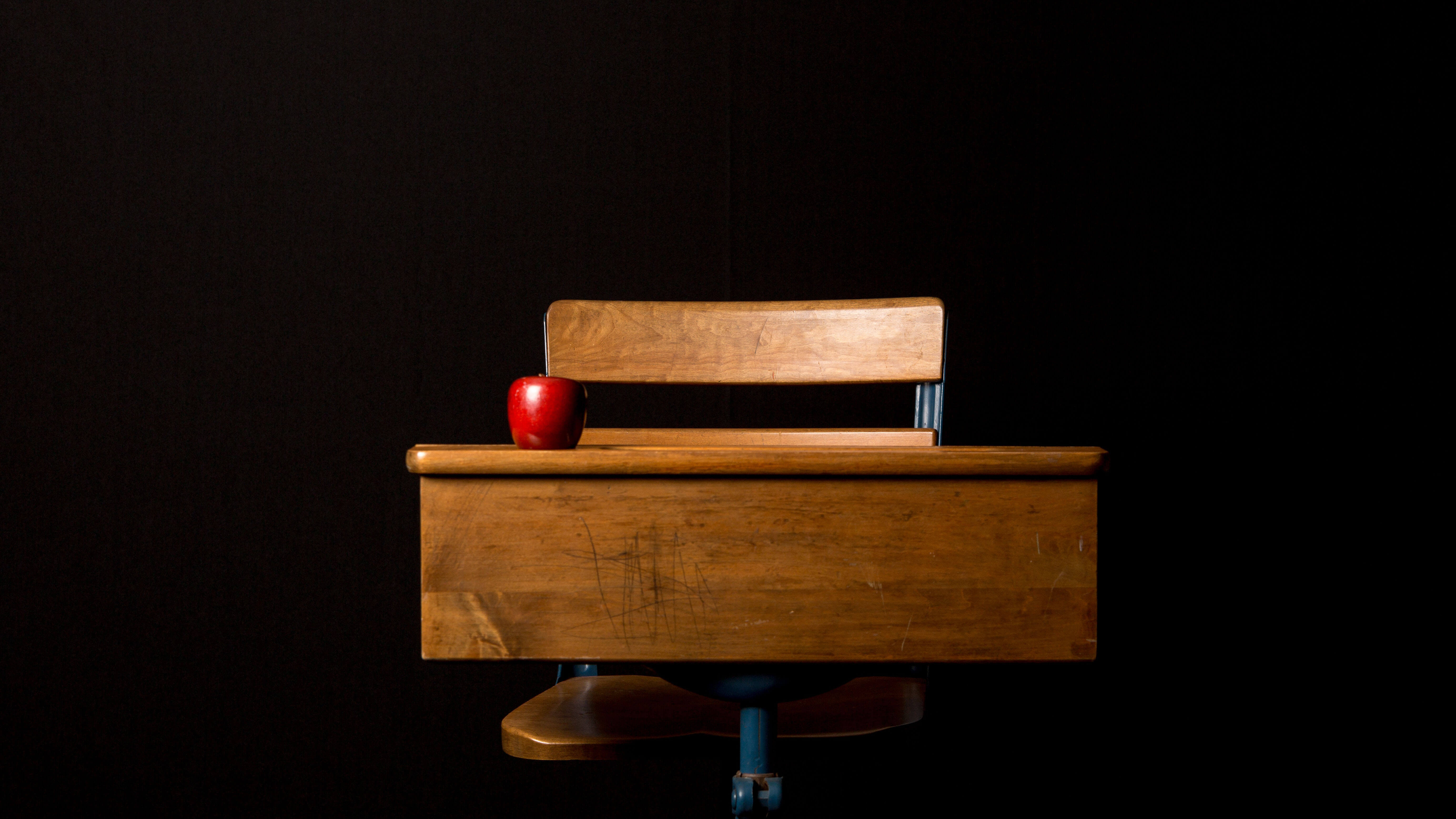 Mesa de estudante com maçã vermelha em cima e fundo preto atrás