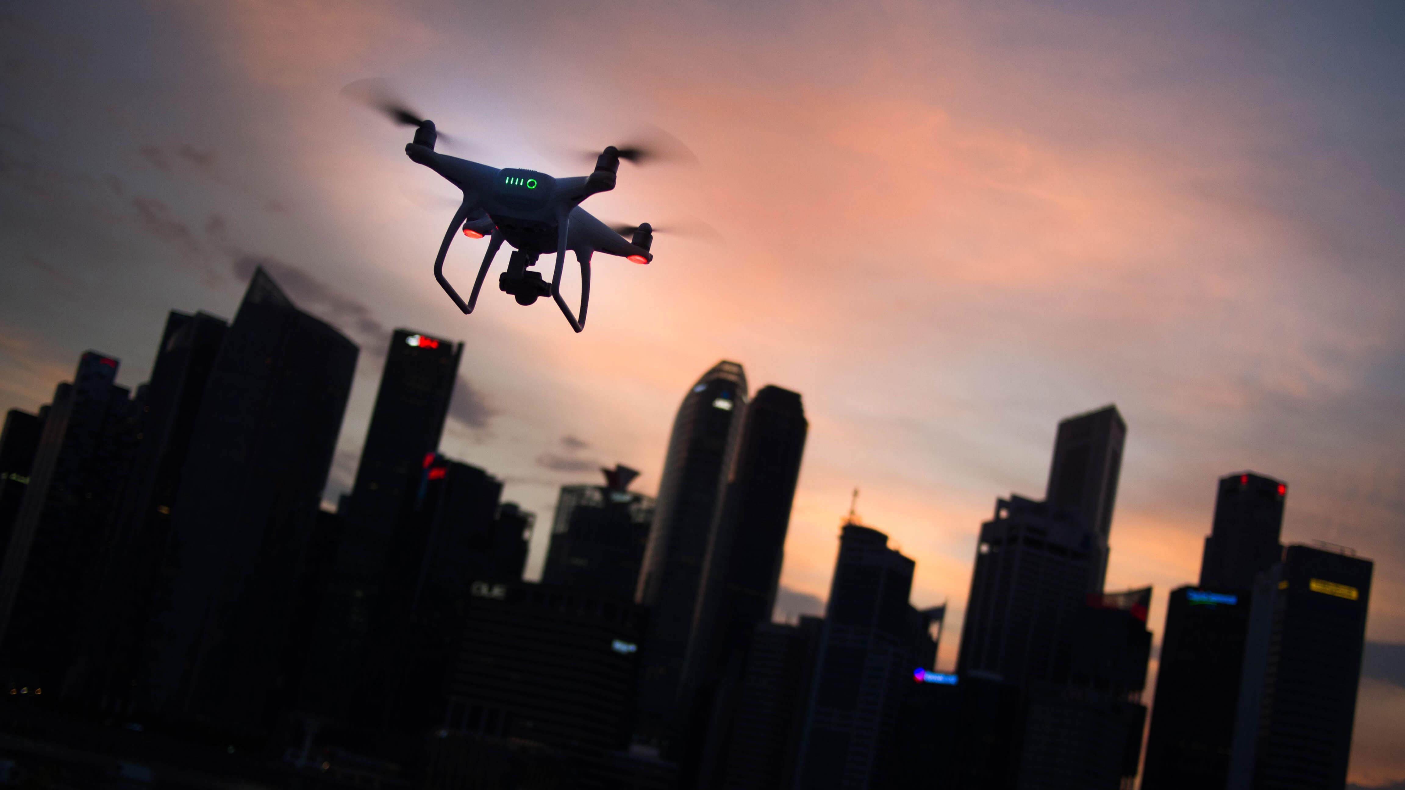 Drone sobrevoando cidade ao entardecer.