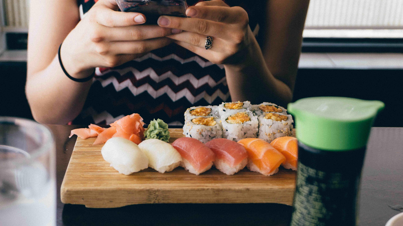 Mulher mexendo no celular com prato de comida japonesa na frente
