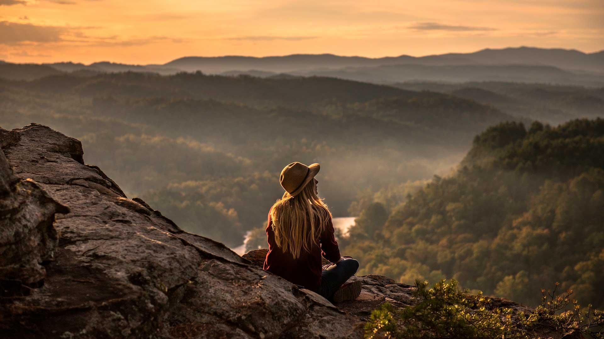 Mulher sentada em montanha observando o pôr do sol no horizonte