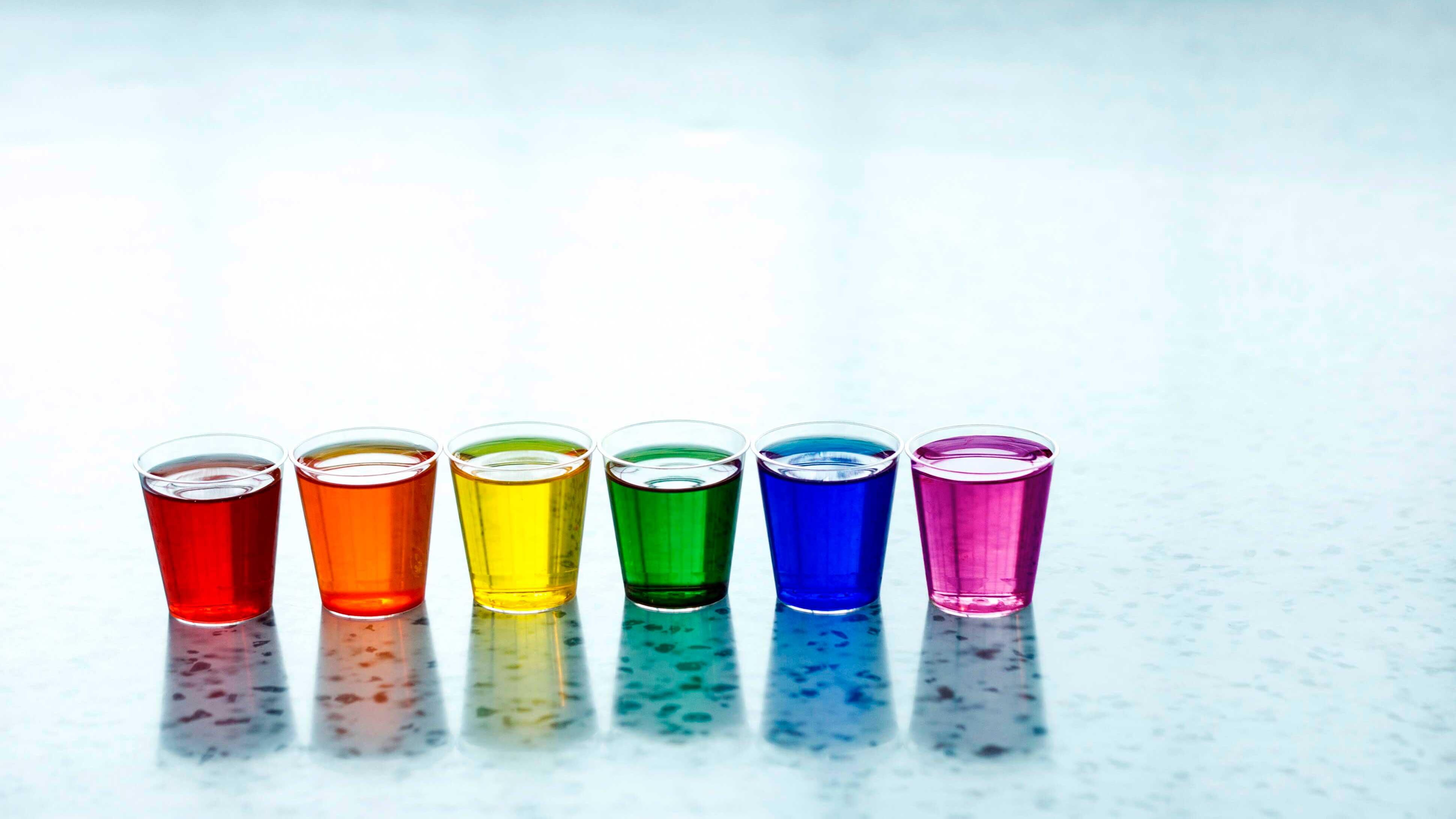 Fileira de copos com líquidos coloridos