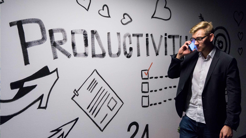 """Homem falando ao celular diante de parede escrito """"Produtividade""""."""