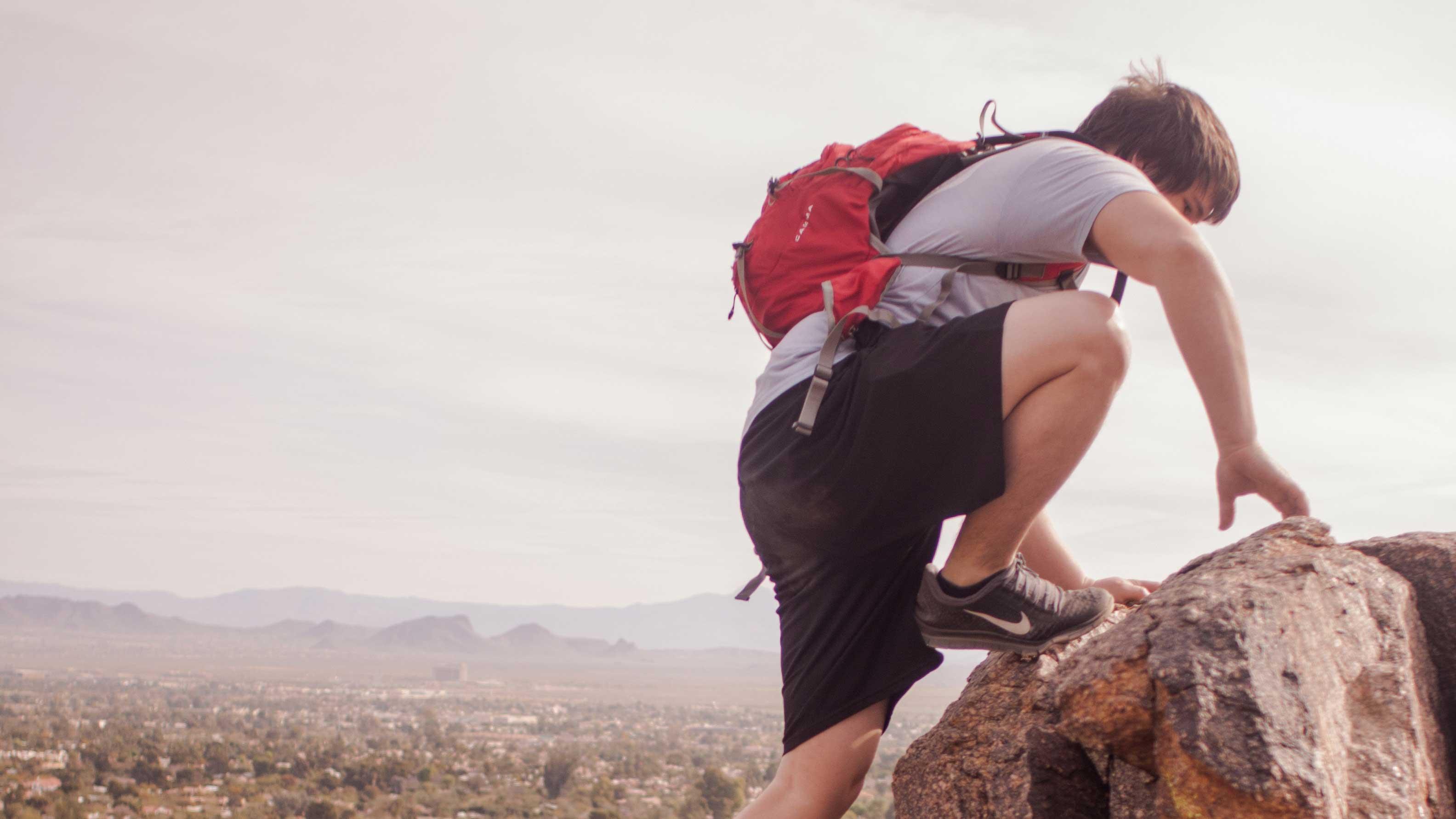 Rapaz escalando montanha