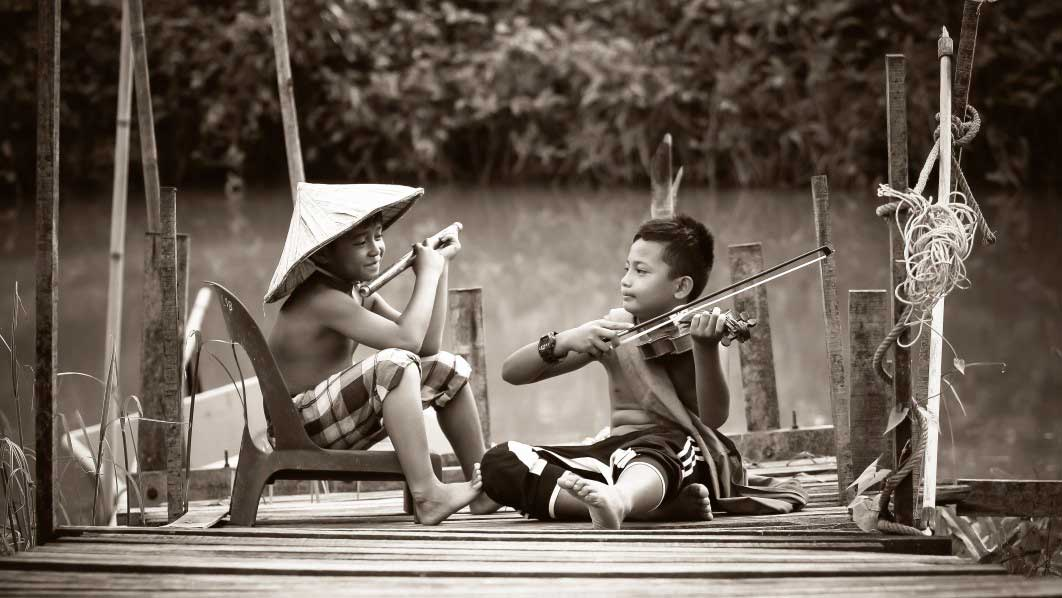 Garotos sentados na beira de lago tocando violinos