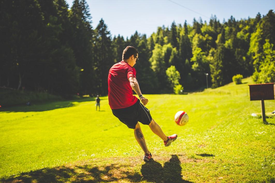 Rapaz jogando futebol em parque