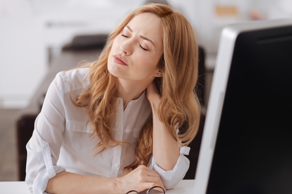 Woman in pain from poor posture at her desk