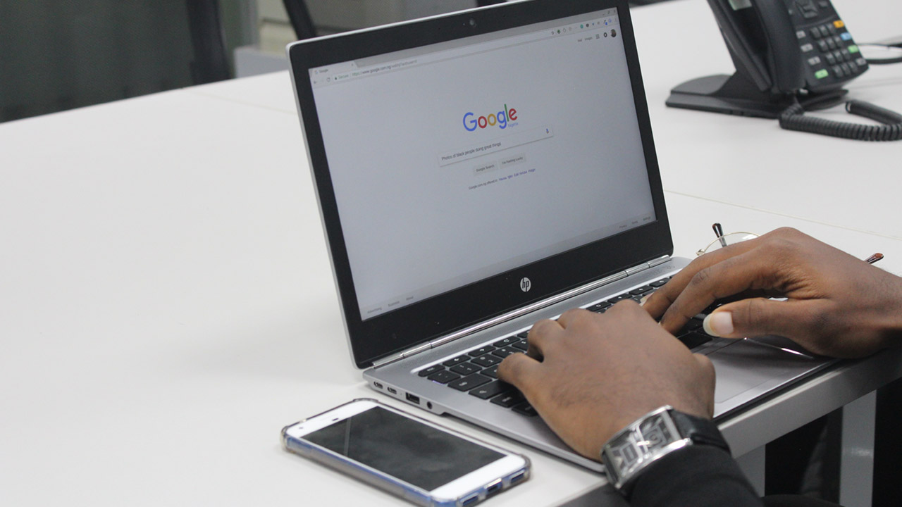 Photo of a person typing a Google search