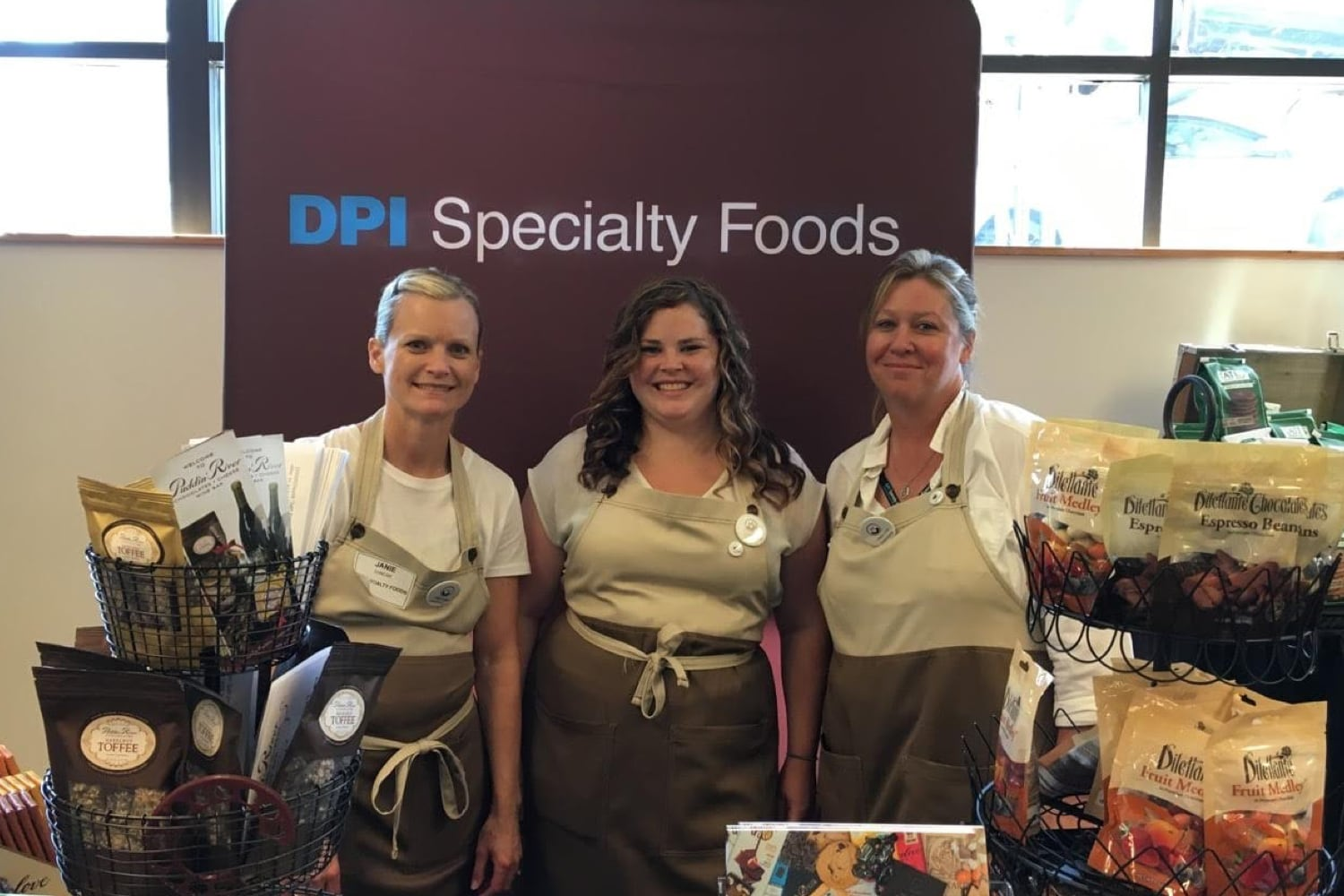 Group of three DPI Specialty Foods employees at their trade show booth