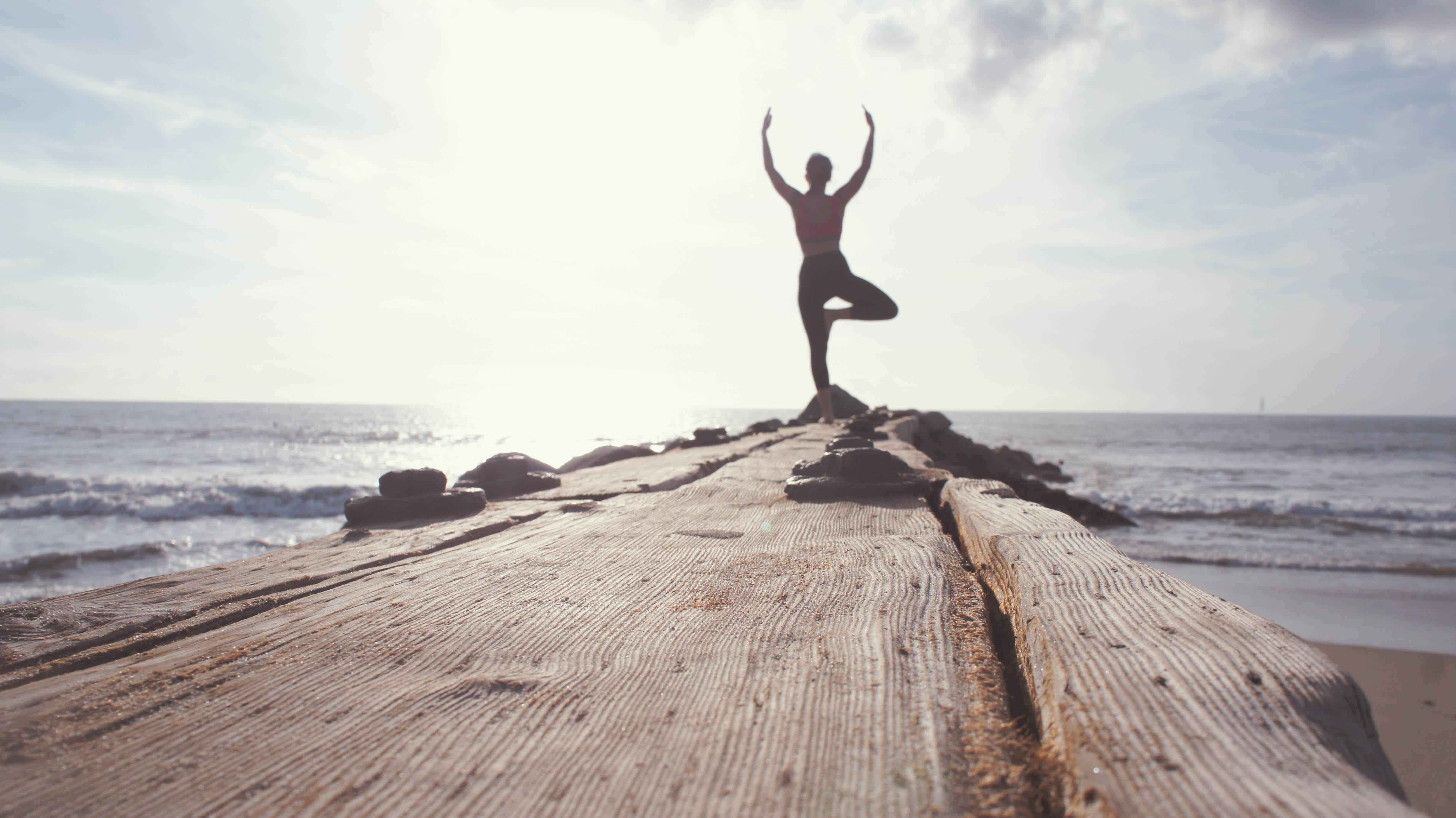 lady doing yoga on a pier
