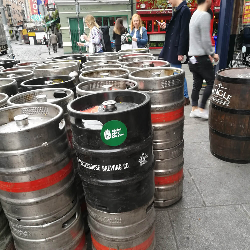 Image of several beer cags and tables blocking the footpath