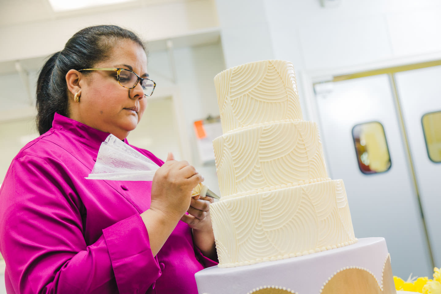 Gina Gutierrez of Cakes by Gina decorating a 3 tier wedding cake
